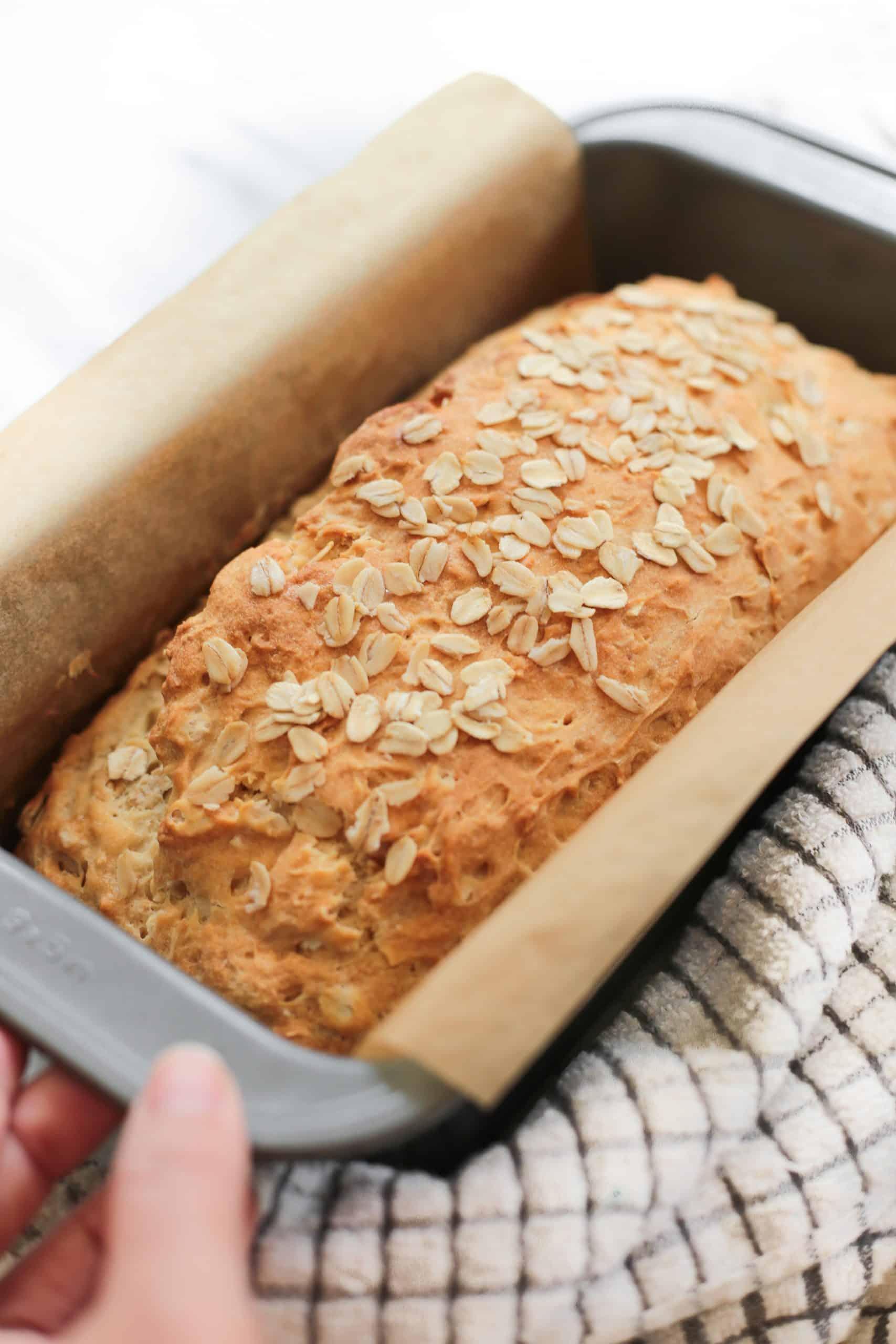 Freshly baked honey oat bread in a pan.
