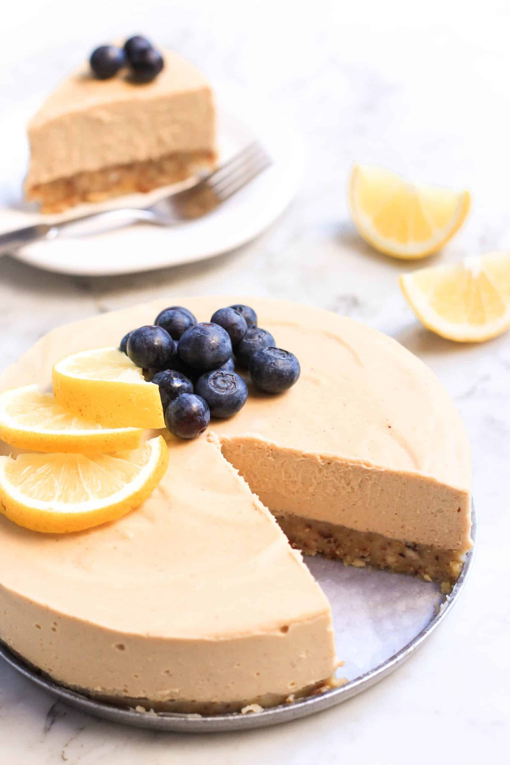 A sliced lemon cheesecake topped with fresh blueberries and lemon slices.