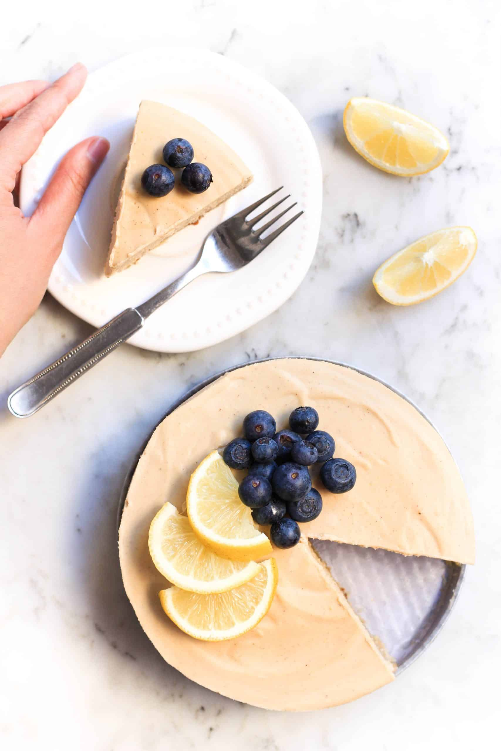Hand holding a plate with a slice of lemon cheesecake.