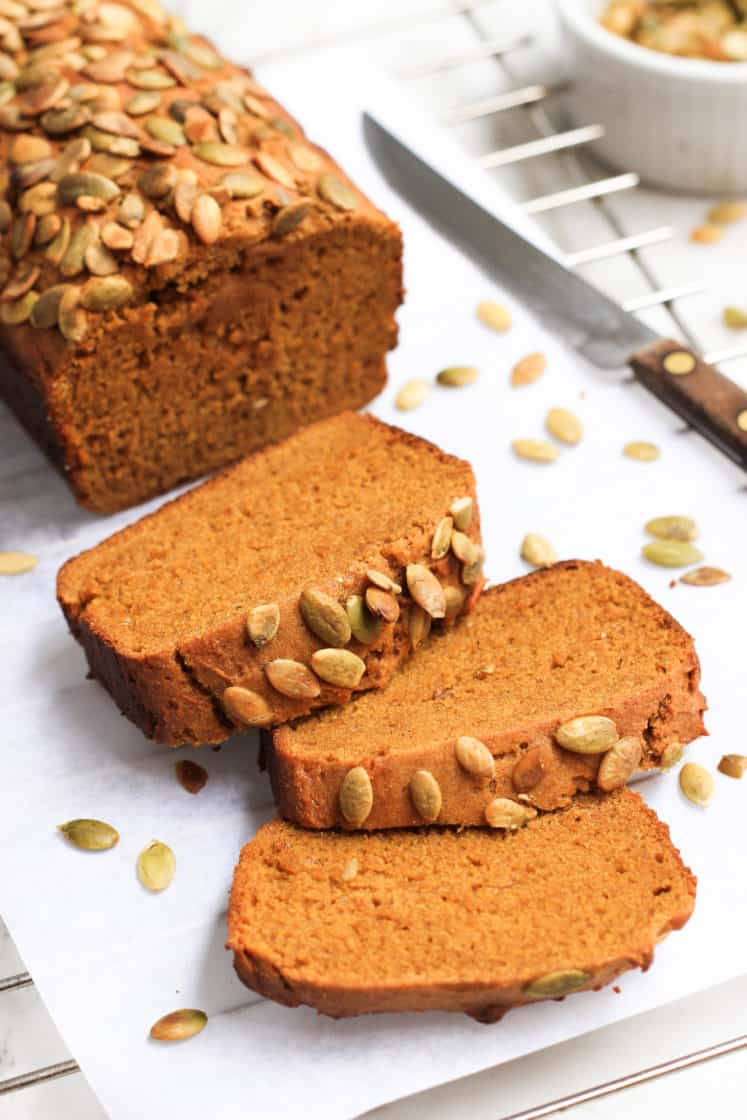 Sliced pumpkin bread surrounded by pumpkin seeds on parchment paper.