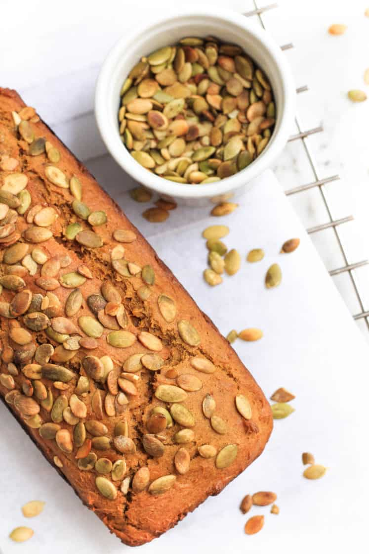A loaf of pumpkin bread on parchment paper surrounded by scatted pumpkin seeds.