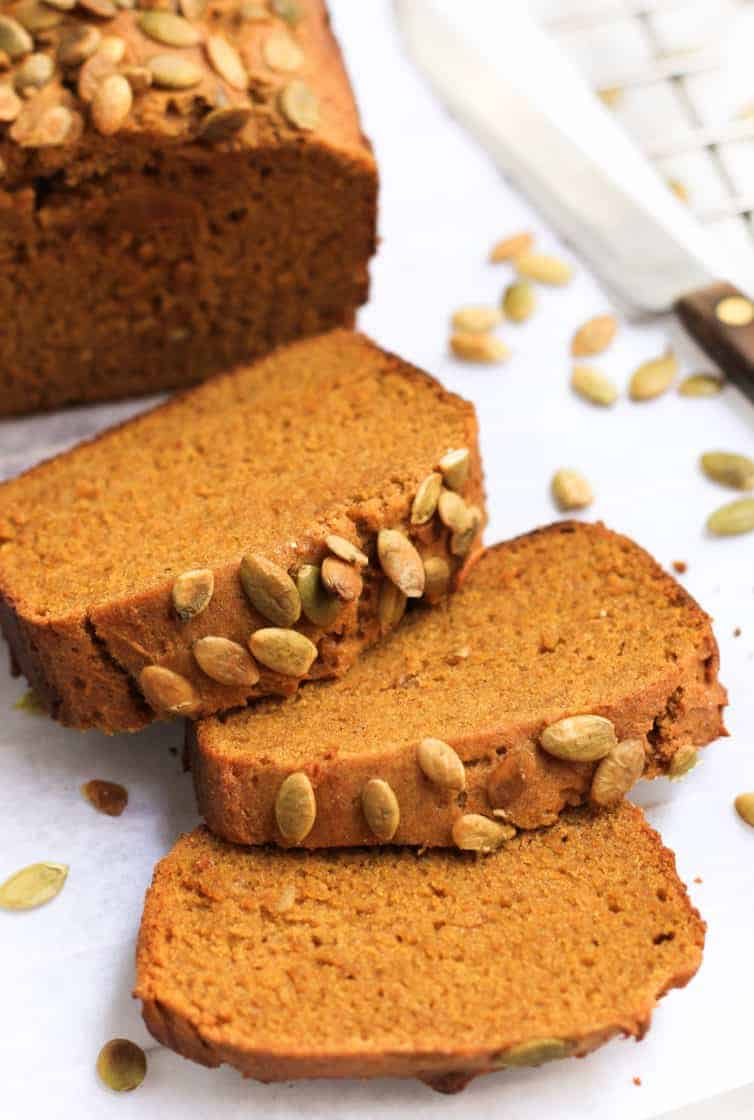 Up close shot of sliced gluten-free pumpkin bread on parchment paper.