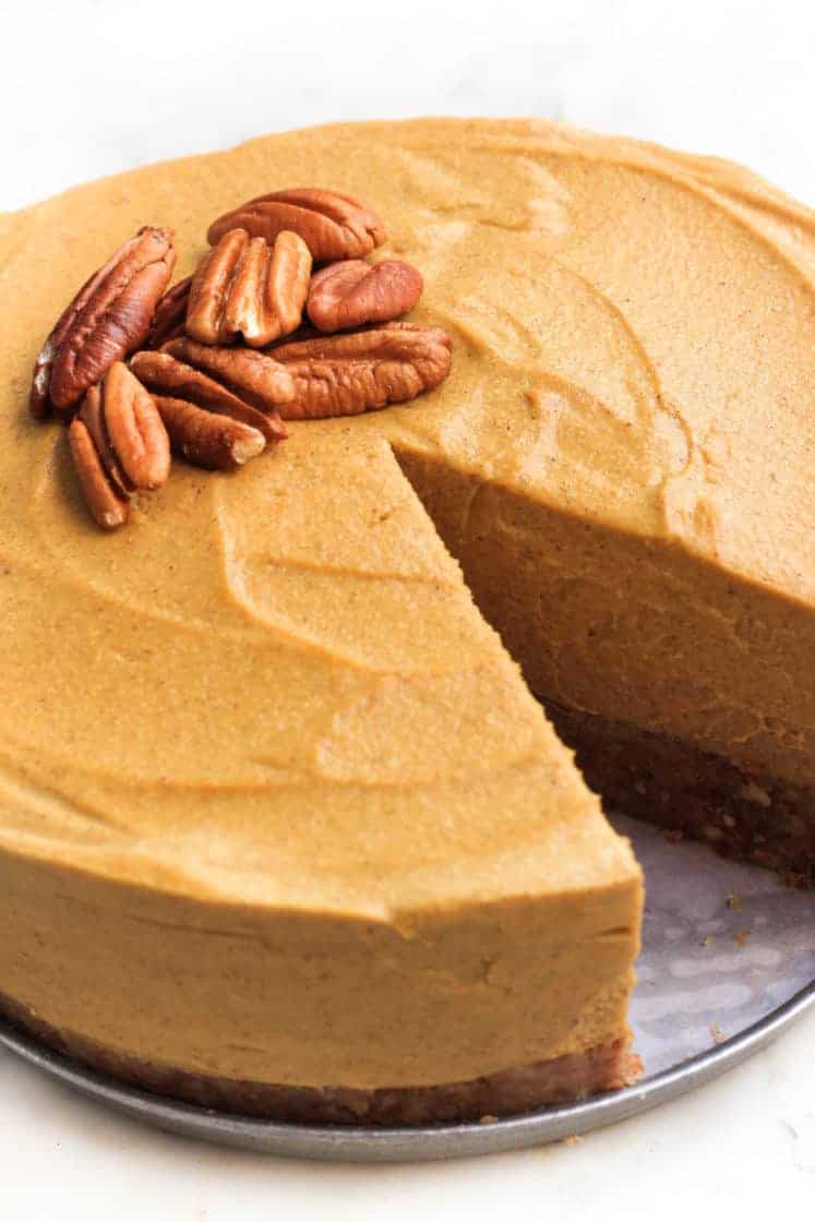 Close up shot of a sliced cheesecake with pecans on top.