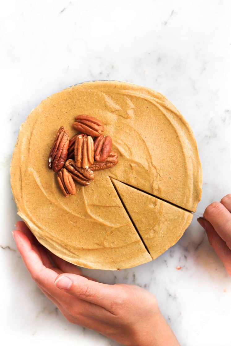 Slicing into a cheesecake topped with whole pecans.