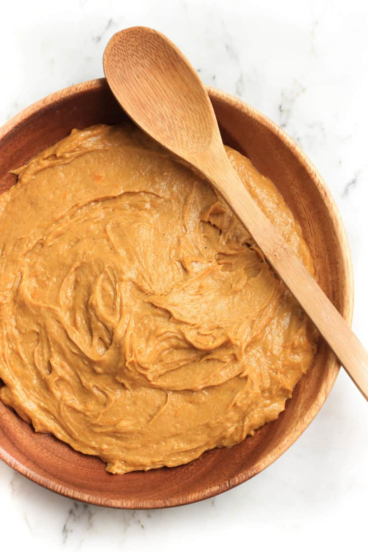 Pumpkin muffin batter mixed together in a wooden bowl.