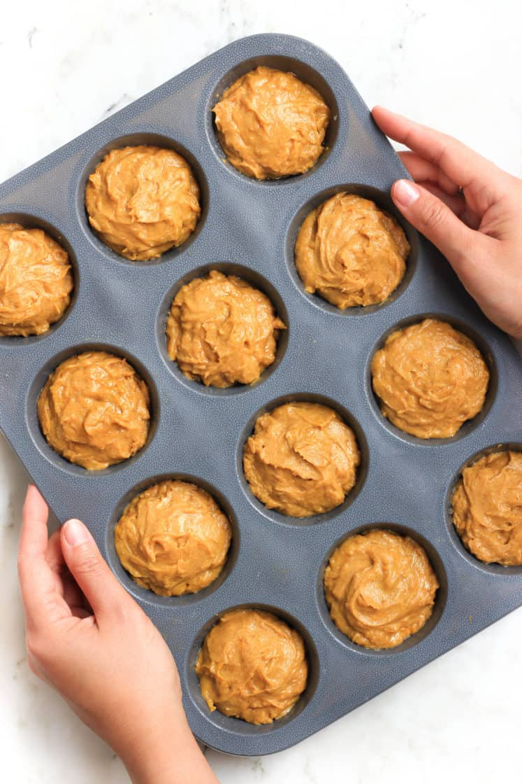 Hands holding a silicon muffin mold filled with muffin batter.