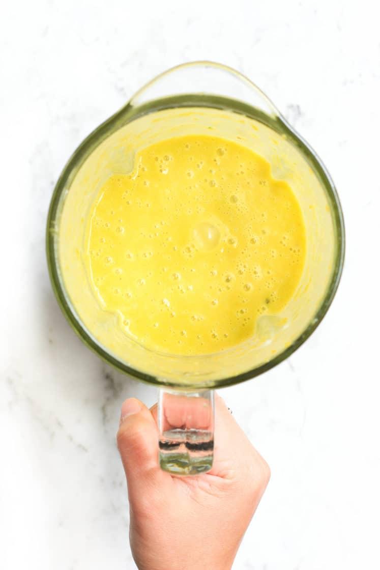 Hand holding a blender with just-blended pumpkin soup.