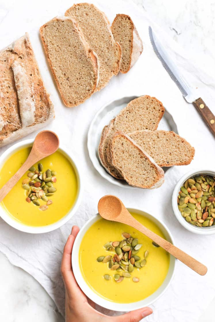 Bowls of soup, slices of bread, and pumpkin seeds on a table.