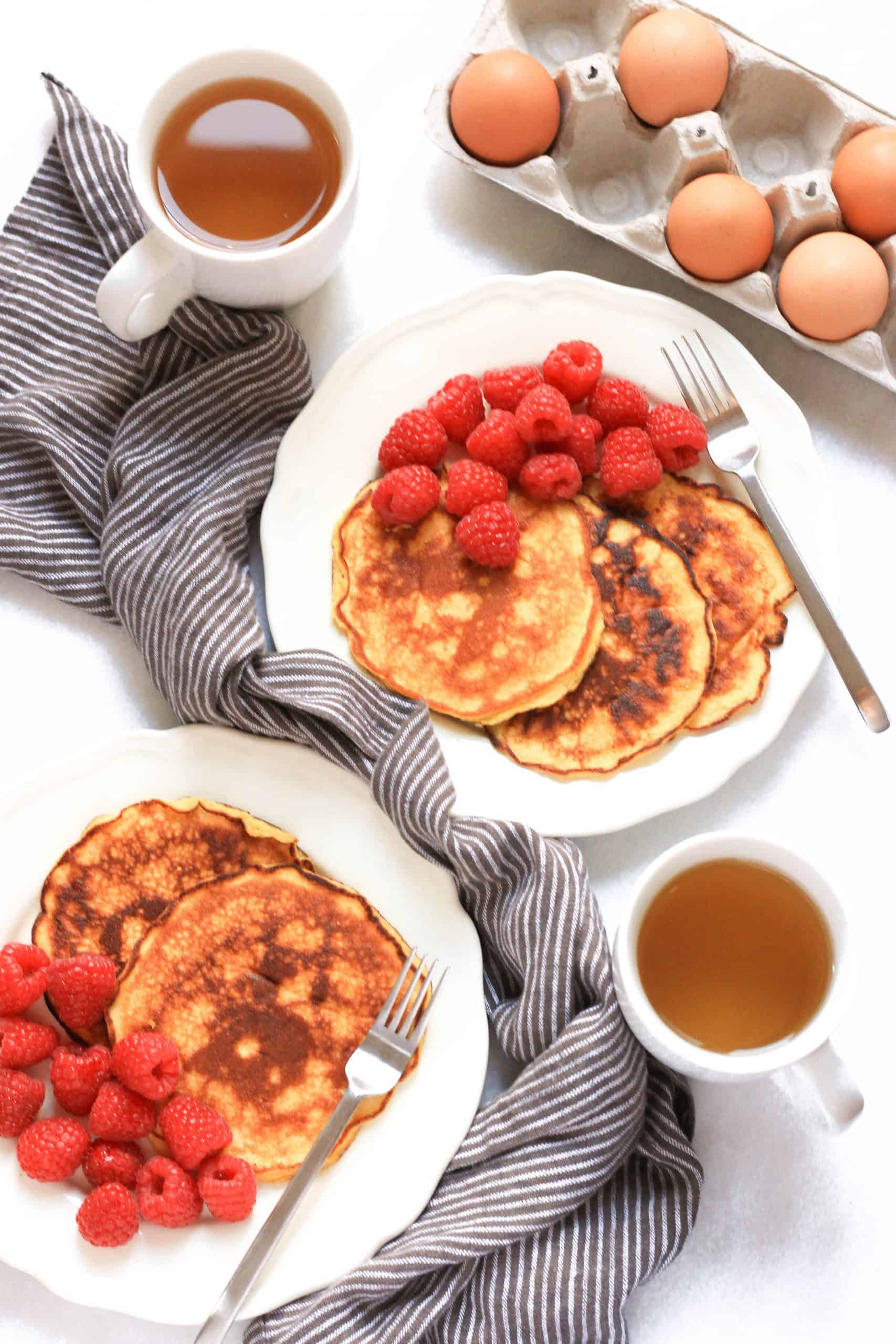 Top down shot of two plates of pancakes with fresh berries and tea.