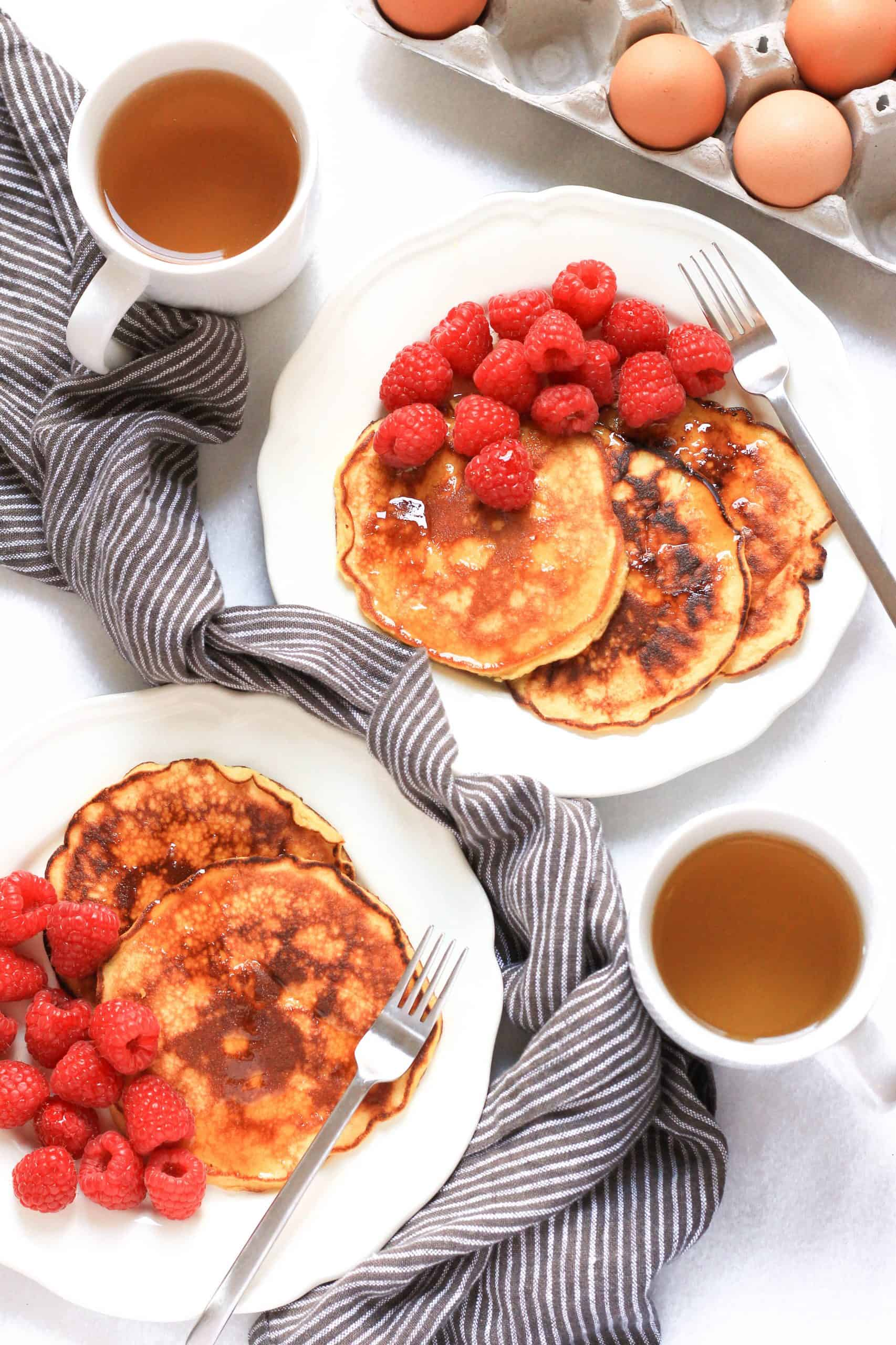 Plates of pancakes and rasberries on a marble board.