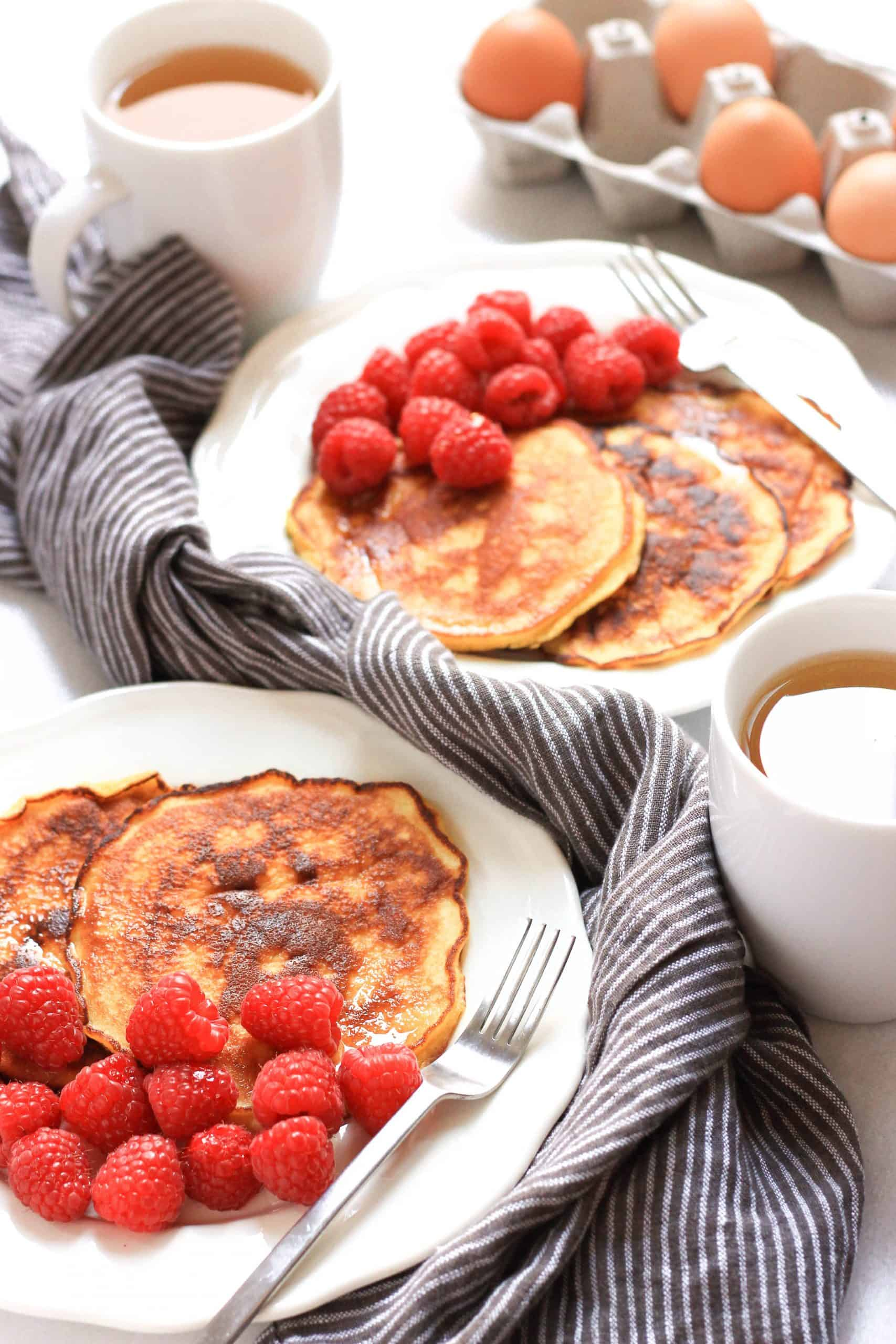 Plates with pancakes and fruits and cups of tea.
