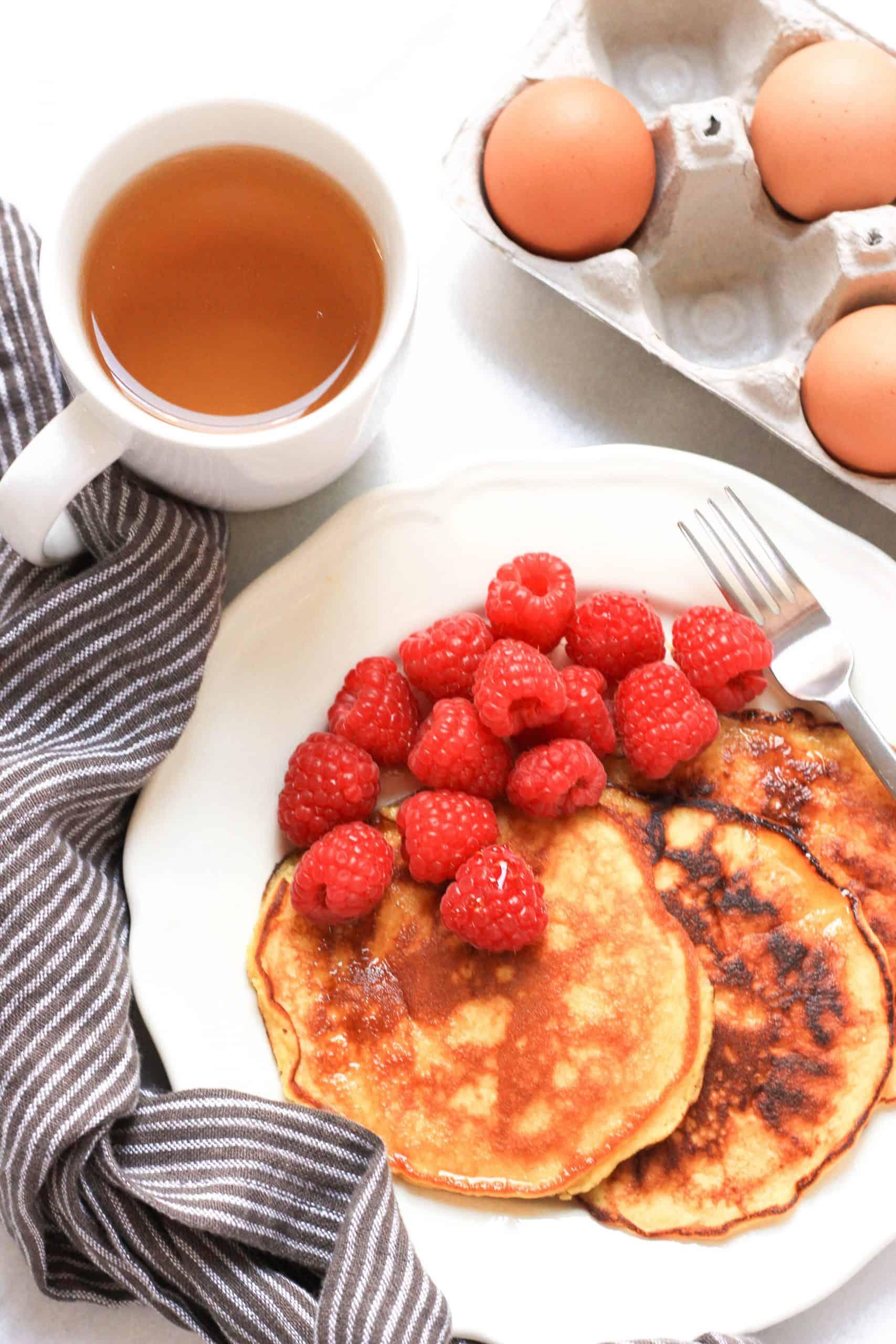 Top down shot of pancakes and raspberries.