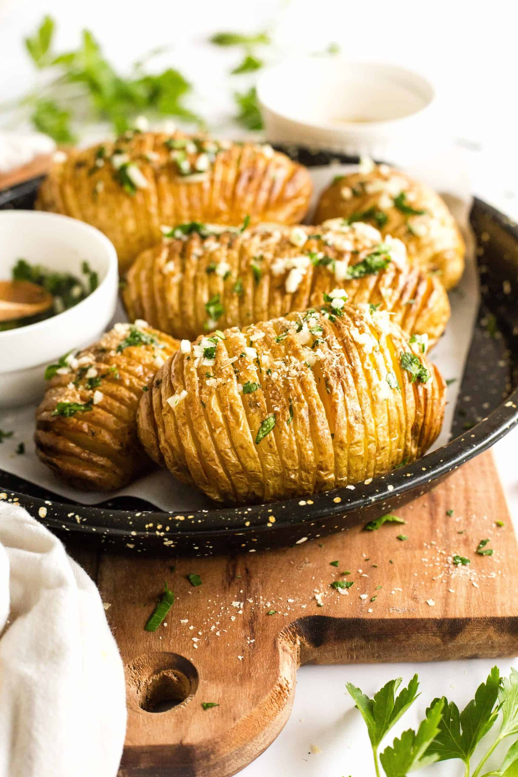 Hasselback potatoes garnished with minced garlic and fresh parsley on w baking sheet on top of a wooden board.