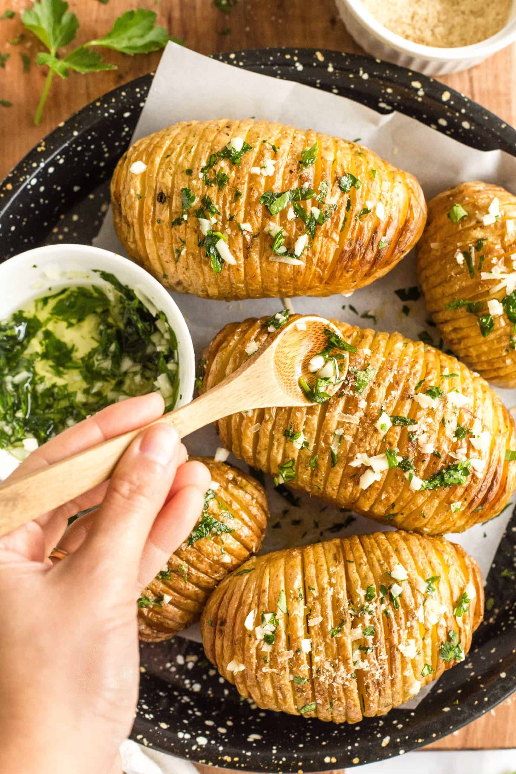 Hand drizzling garlic-parsley sauce over freshly cooked hasselback potatoes.