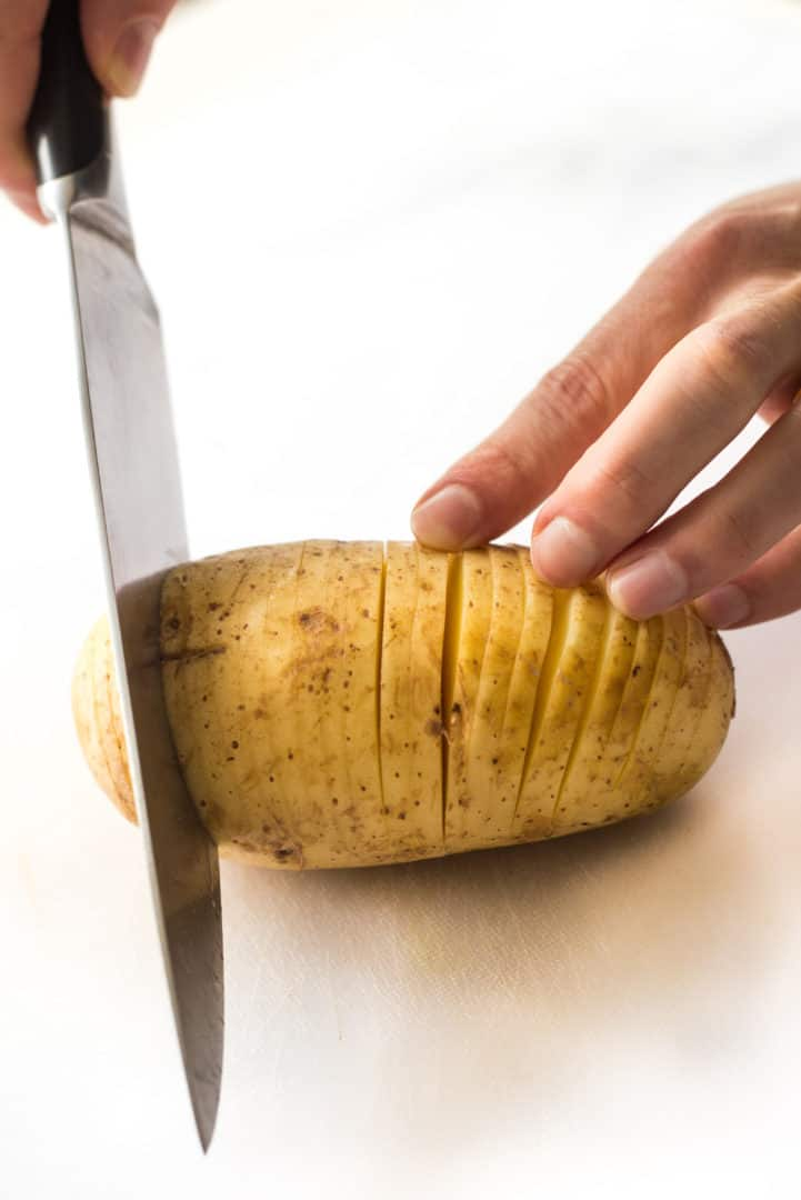 Hand slicing a yukon gold potato in thin fans to create Hasselback potatoes.