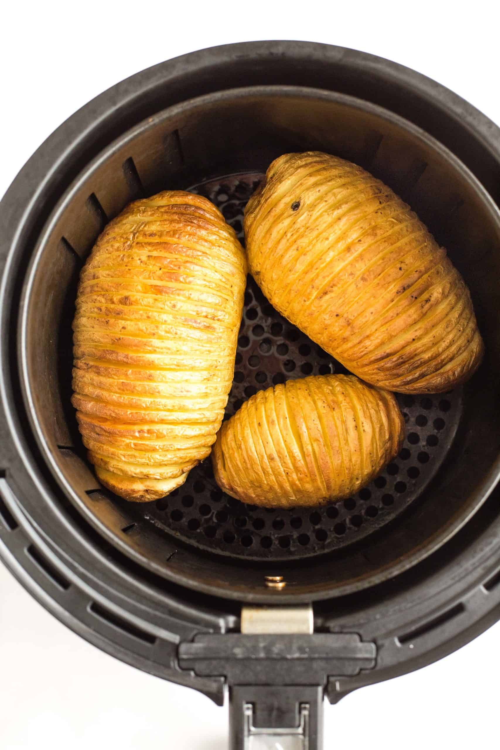 Crispy hasselback potatoes in the air fryer basket.