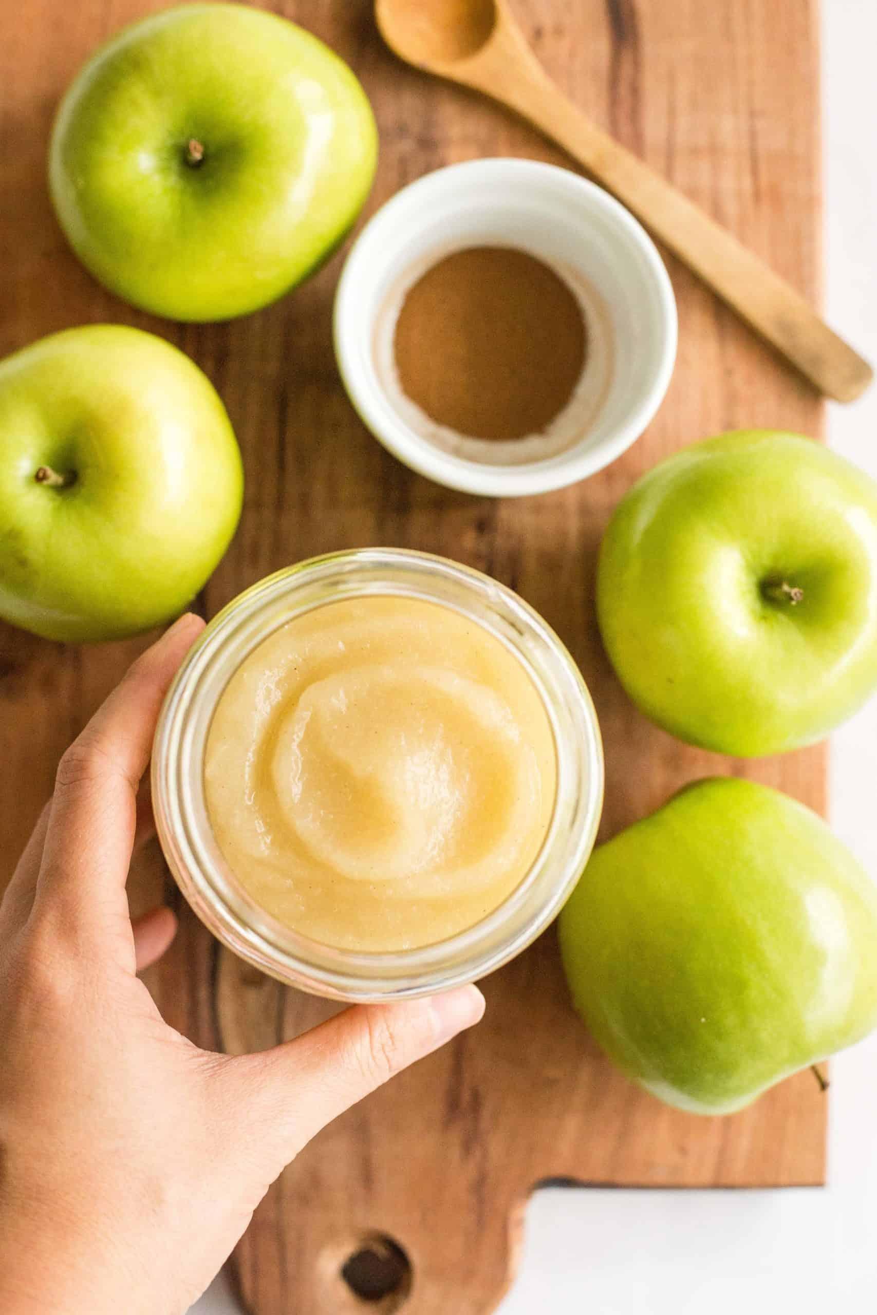Hand holding a jar of homemade applesauce.