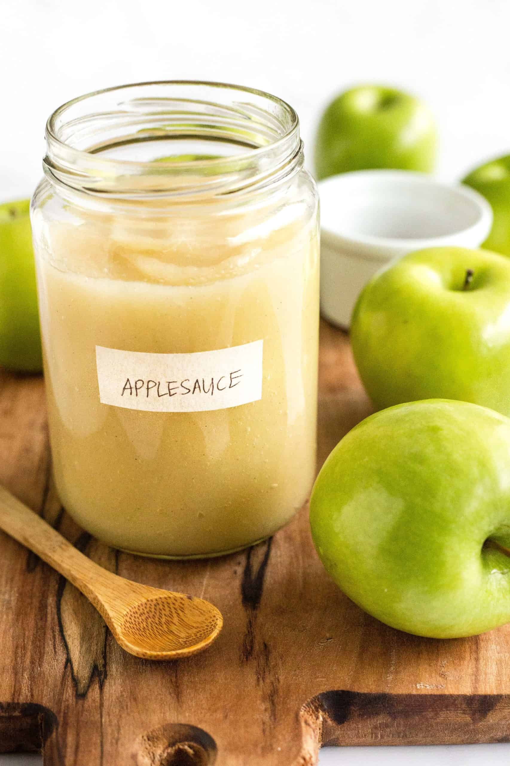 A jar of freshly made homemade applesauce surrounded by green apples on a wooden board.