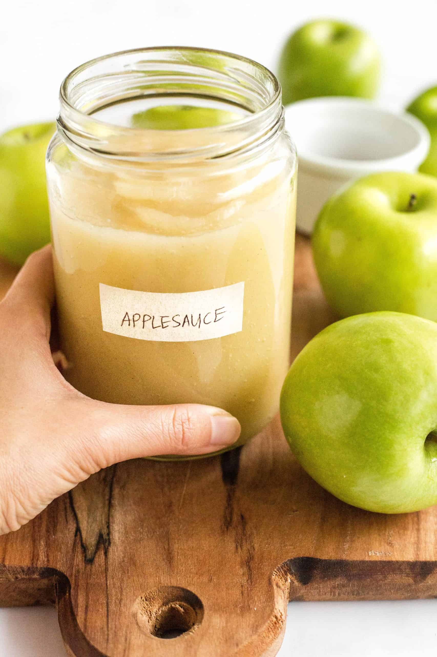 Hand holding a jar for fresh homemade applesauce.