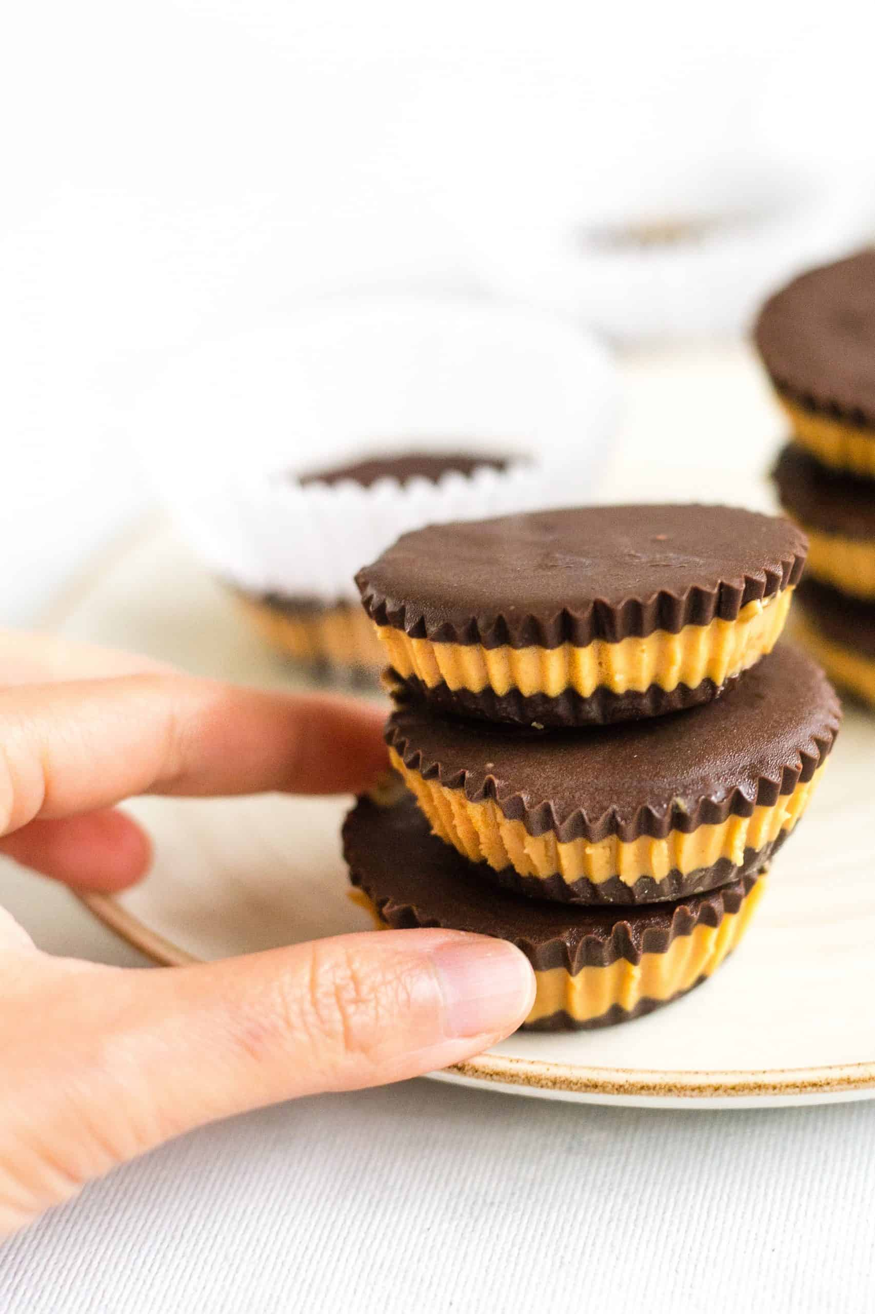 Hand reaching for a stack of chocolate peanut butter cups on a plate.