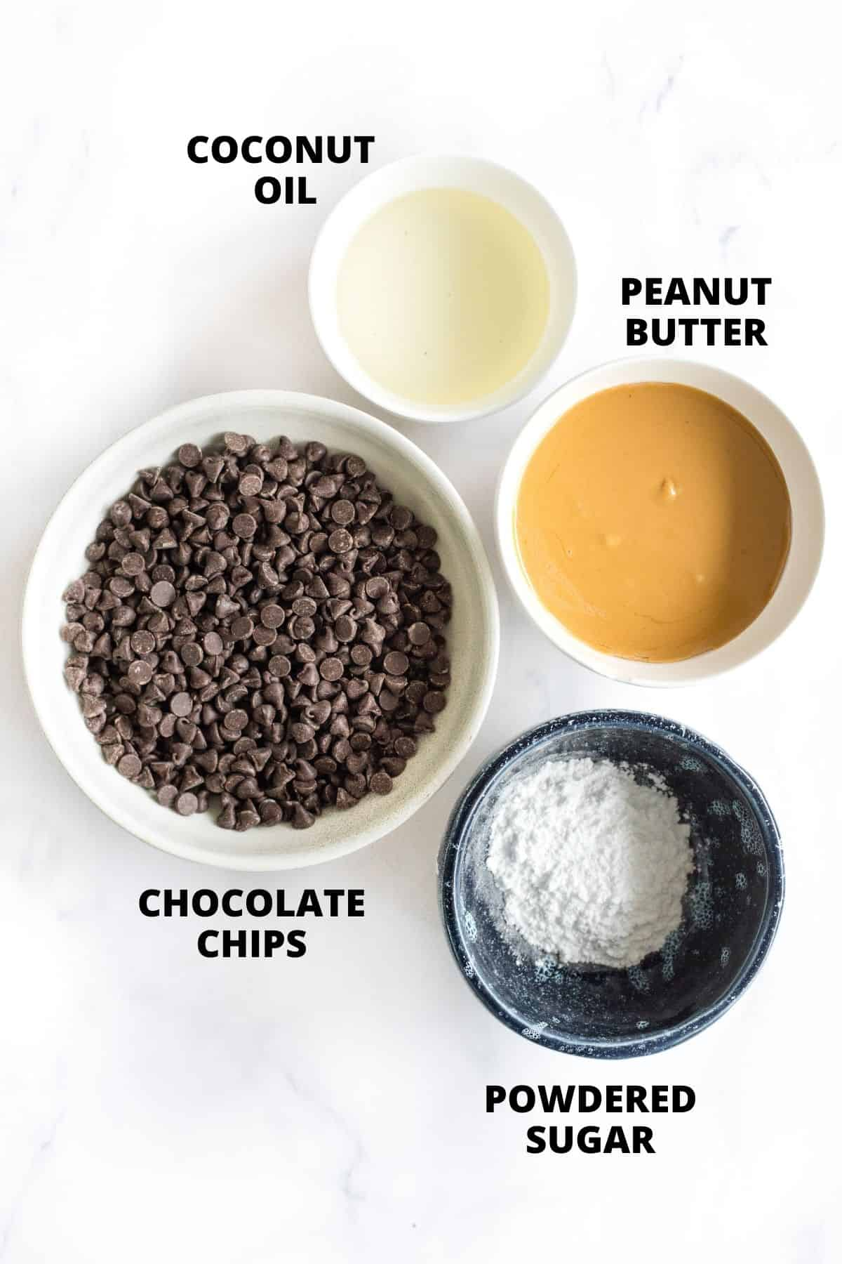 Labeled ingredients for homemade peanut butter cups on a marble board.