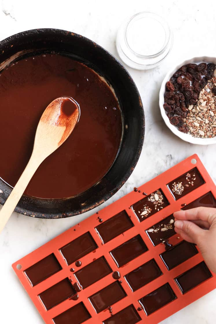 Sprinkling seeds over chocolate mixture in a silicon mold.