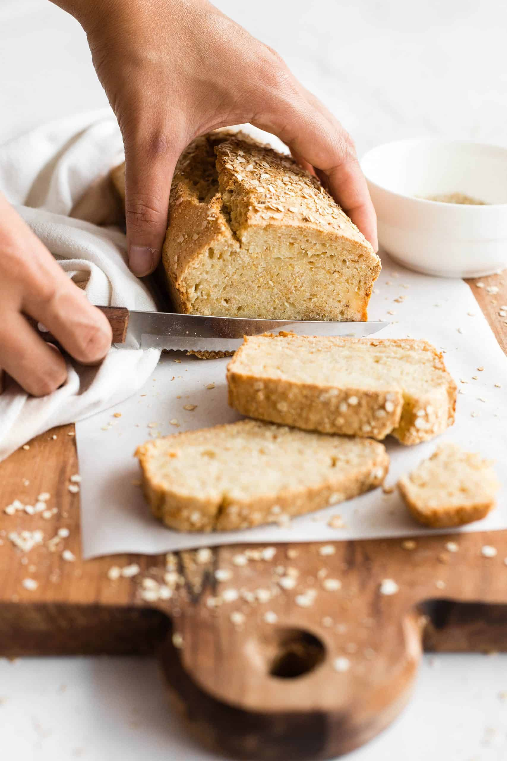 Slicing a loaf of honey quinoa bread on a parchment-lined wooden board.