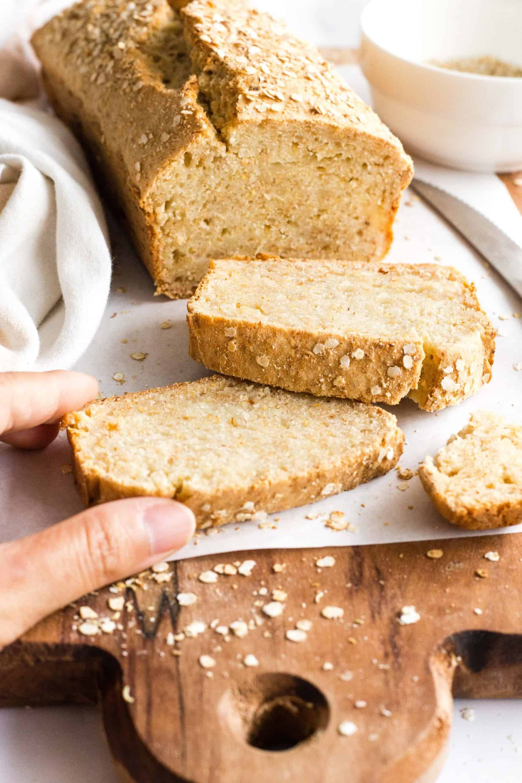 Hand reaching for a slice of quinoa bread.