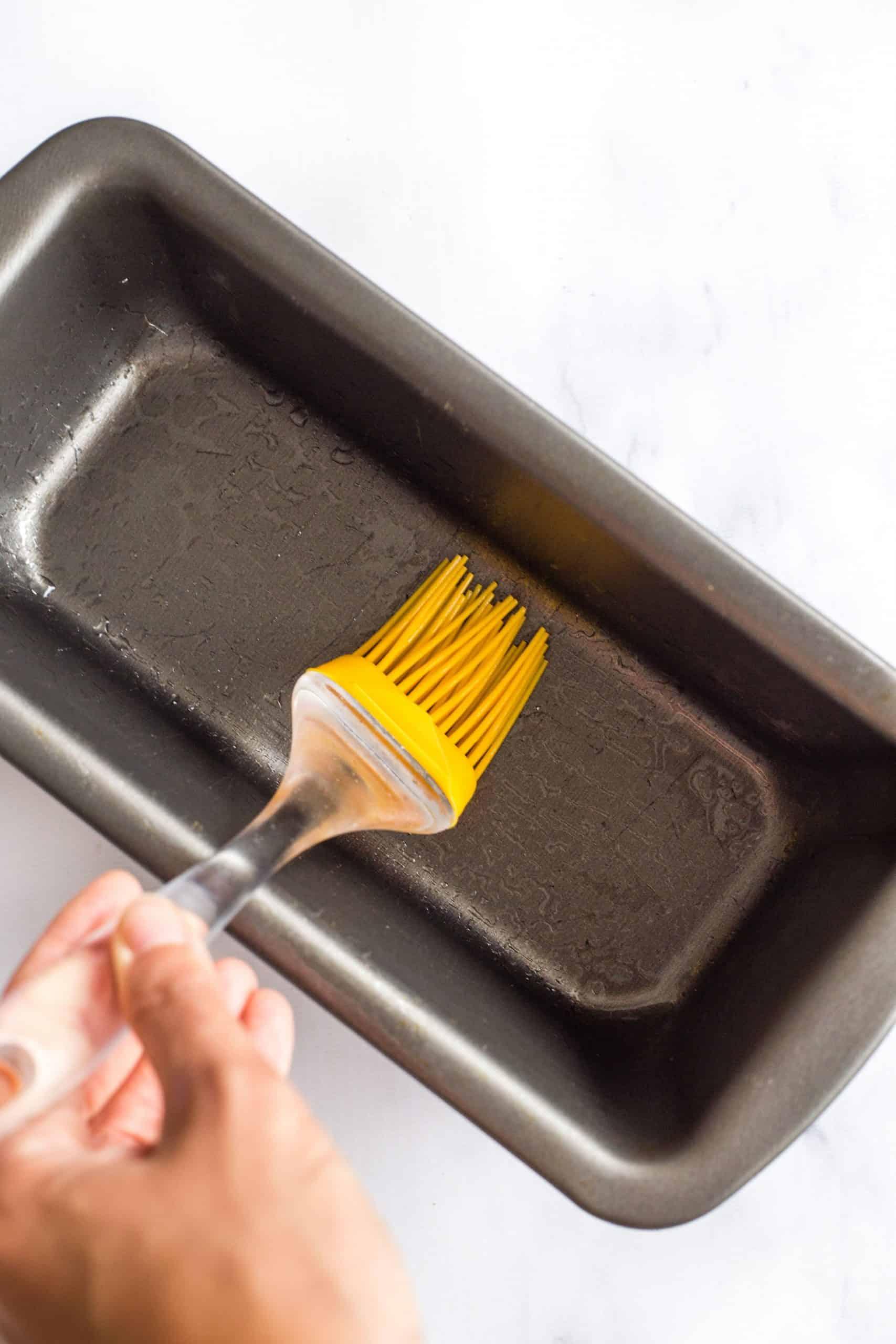 Greasing a metal loaf pan.