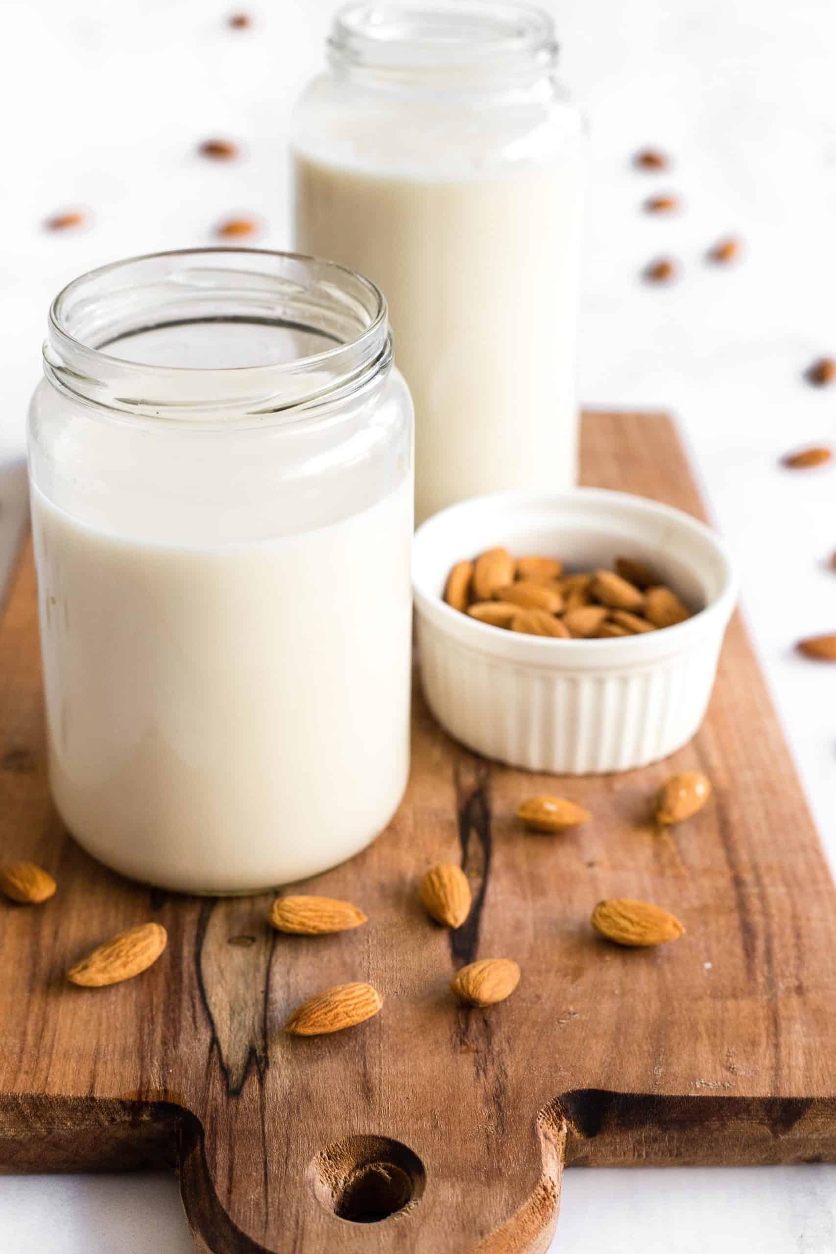 Bottles of freshly made almond milk on a wooden board.