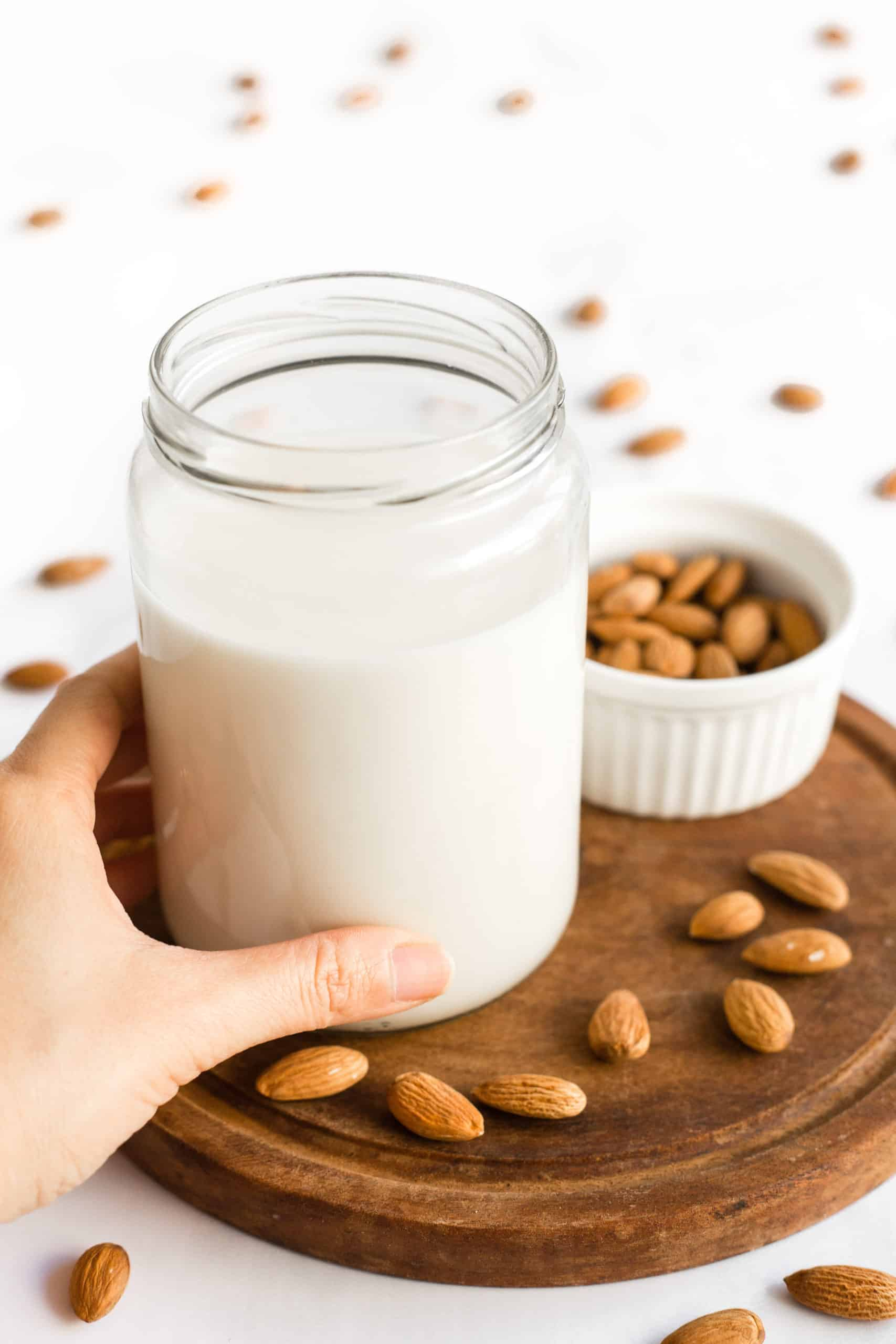 Hand holding a jar of homemade almond milk.