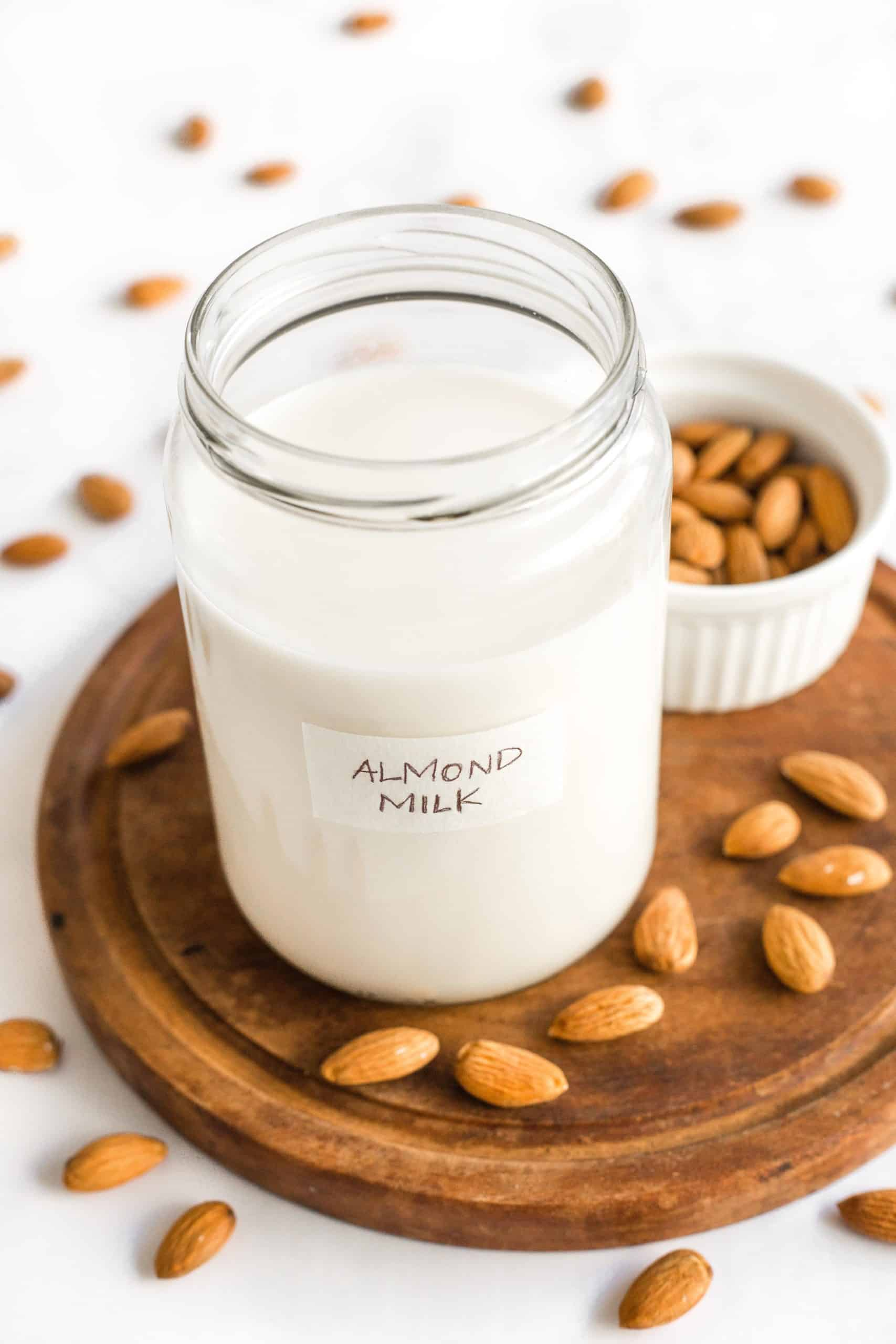 A jar of homemade almond milk on a wooden board surrounded by raw almonds.