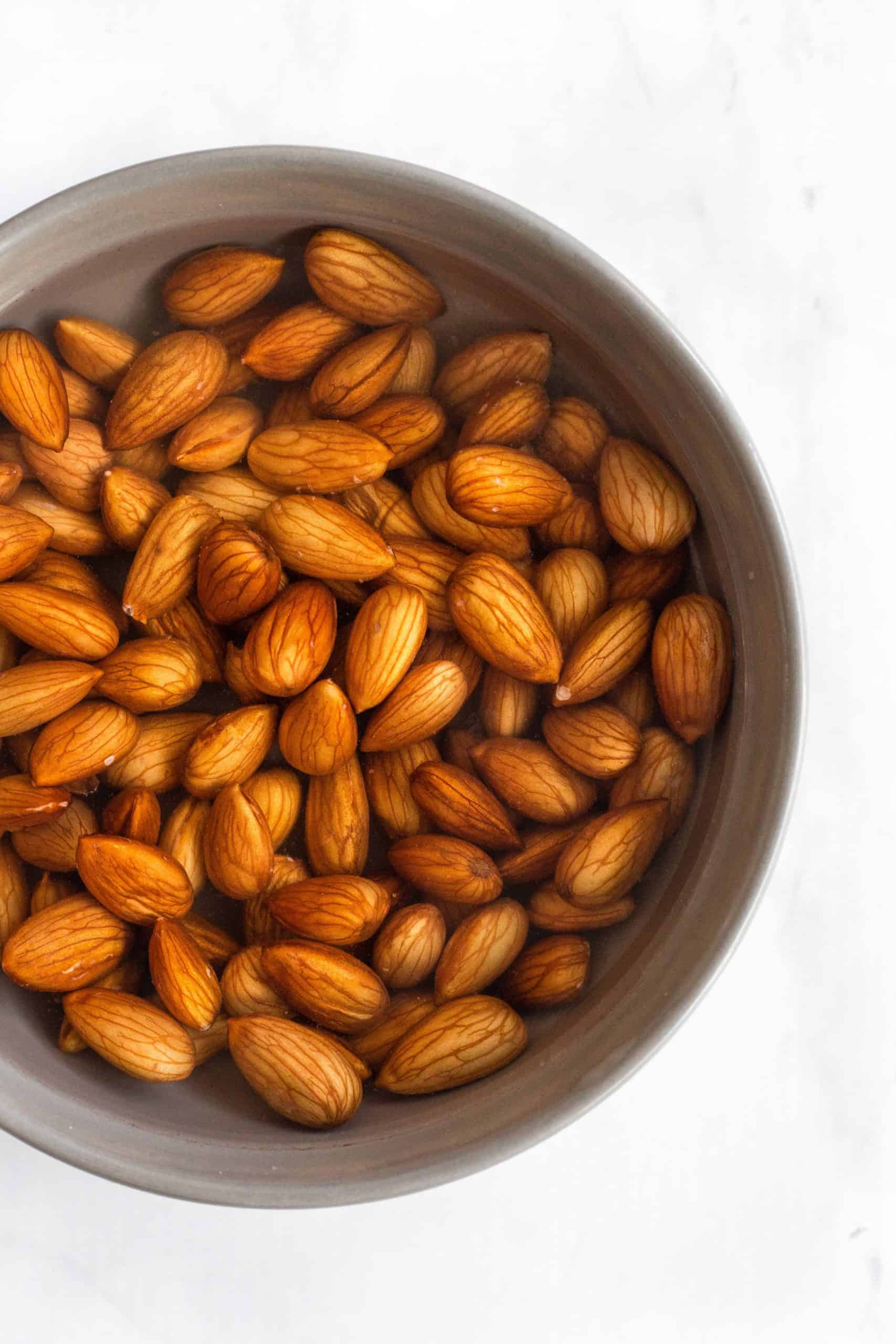 Raw almonds soaking in a bowl of water.