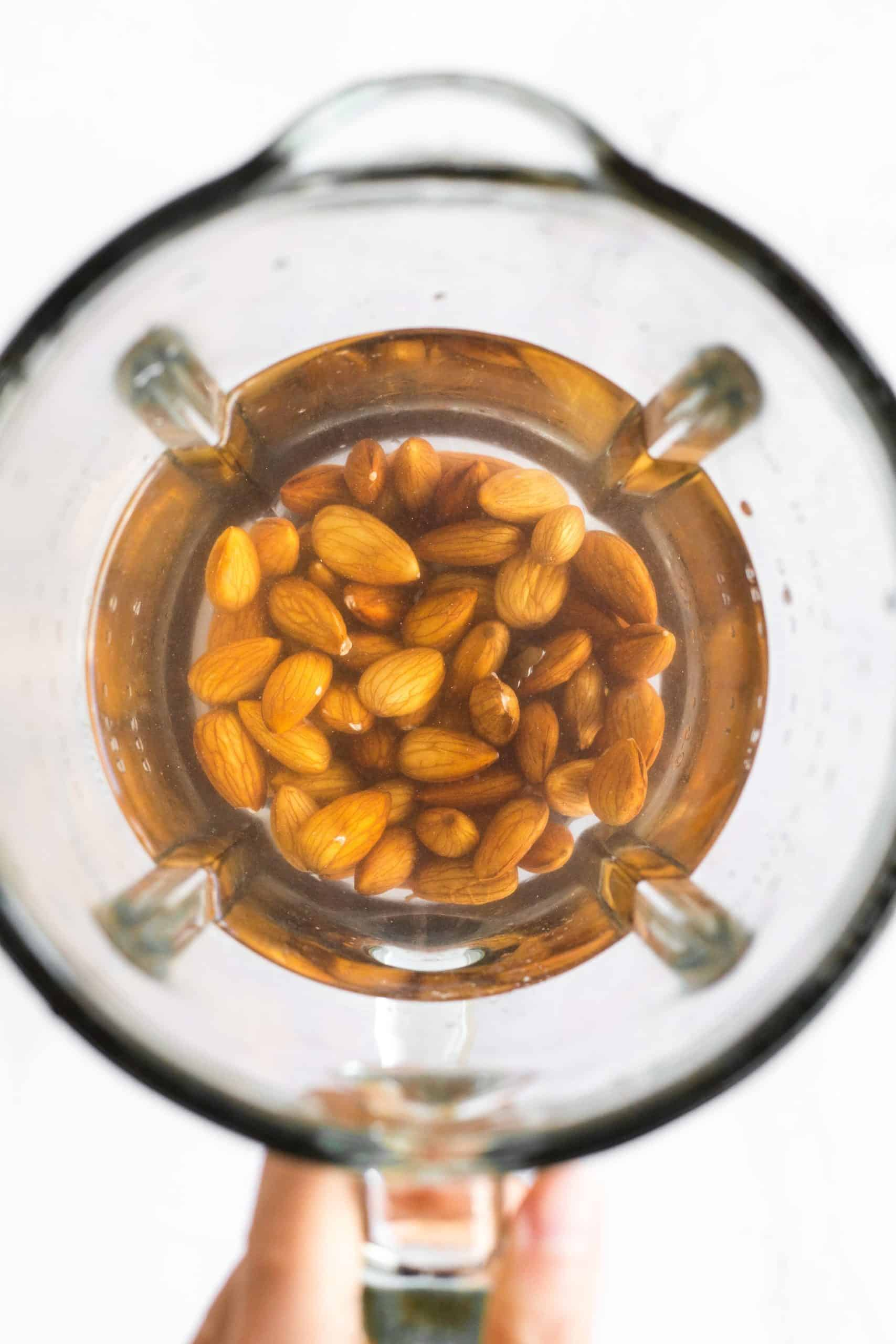 Raw almonds a water in a the bowl of a blender.