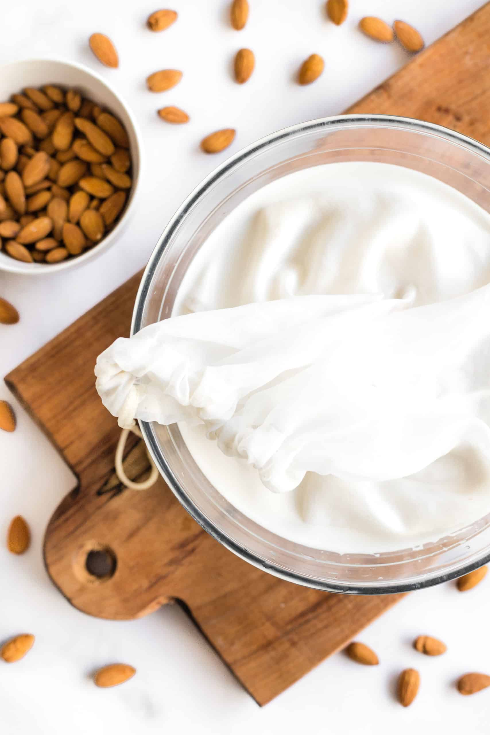 A bowl of almond milk ready to be strained with a nut milk bag.