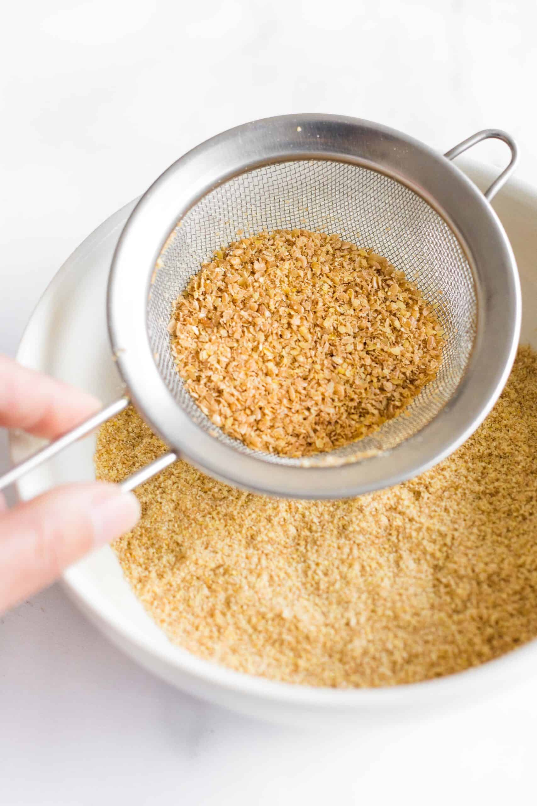 Sifting golden flaxseed meal through a fine mesh sieve.