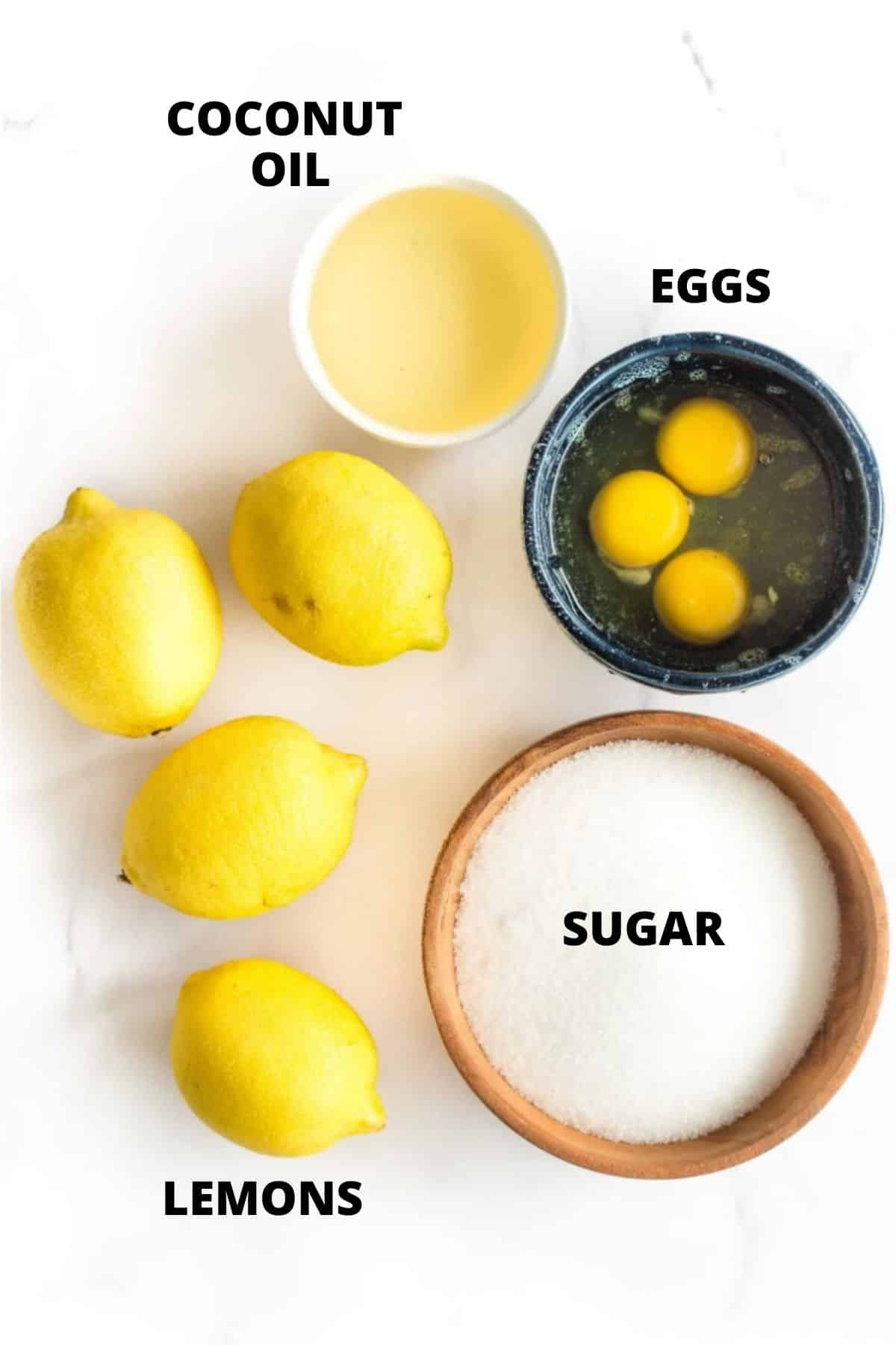 Ingredients for lemon curd on a marble board (eggs, sugar, lemon, and coconut oil).