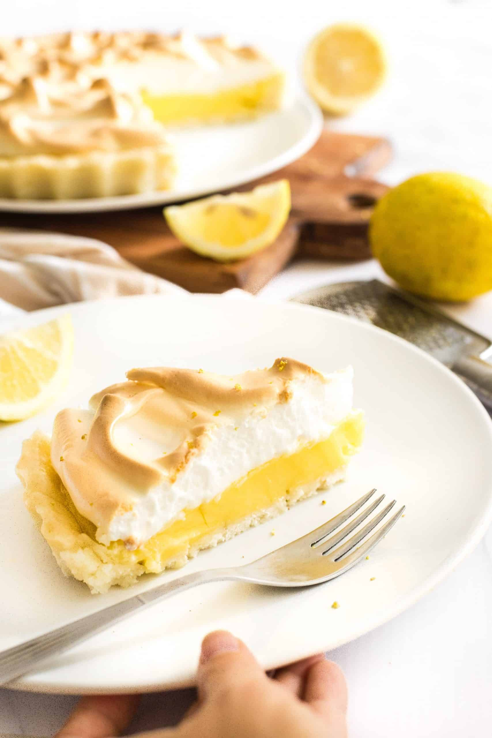 Holding onto a plate with a slice of lemon meringue pie.