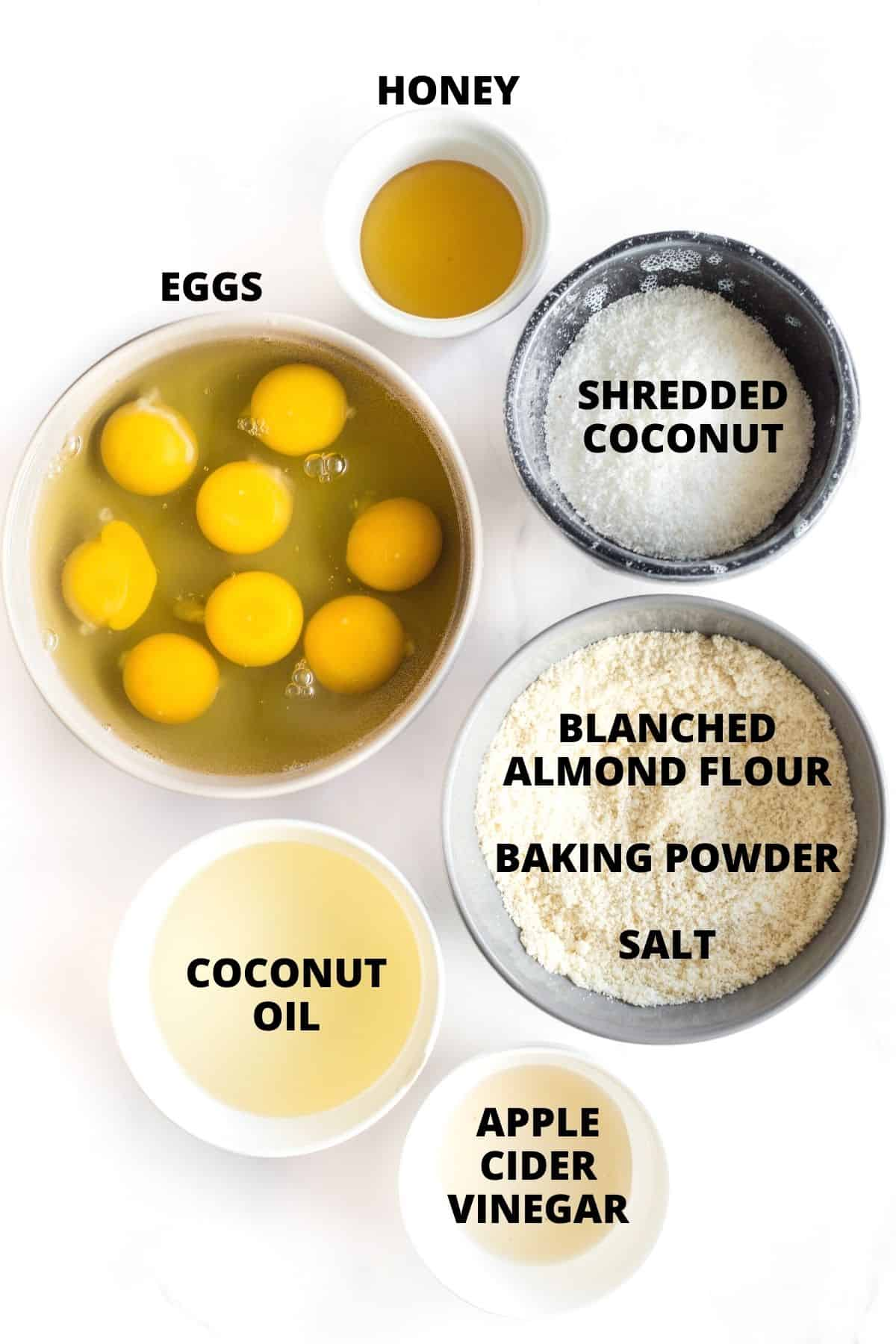Labeled ingredients for almond flour bread laid out on marble board.