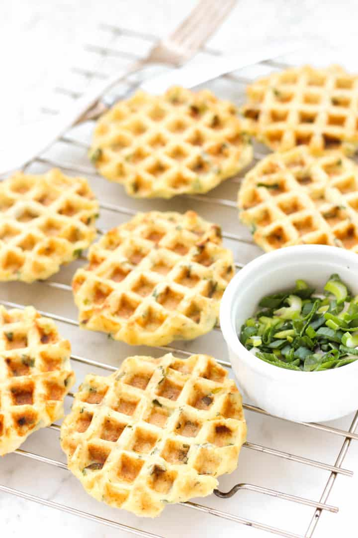 Mashed potato and spring onion waffles on a cooling rack.