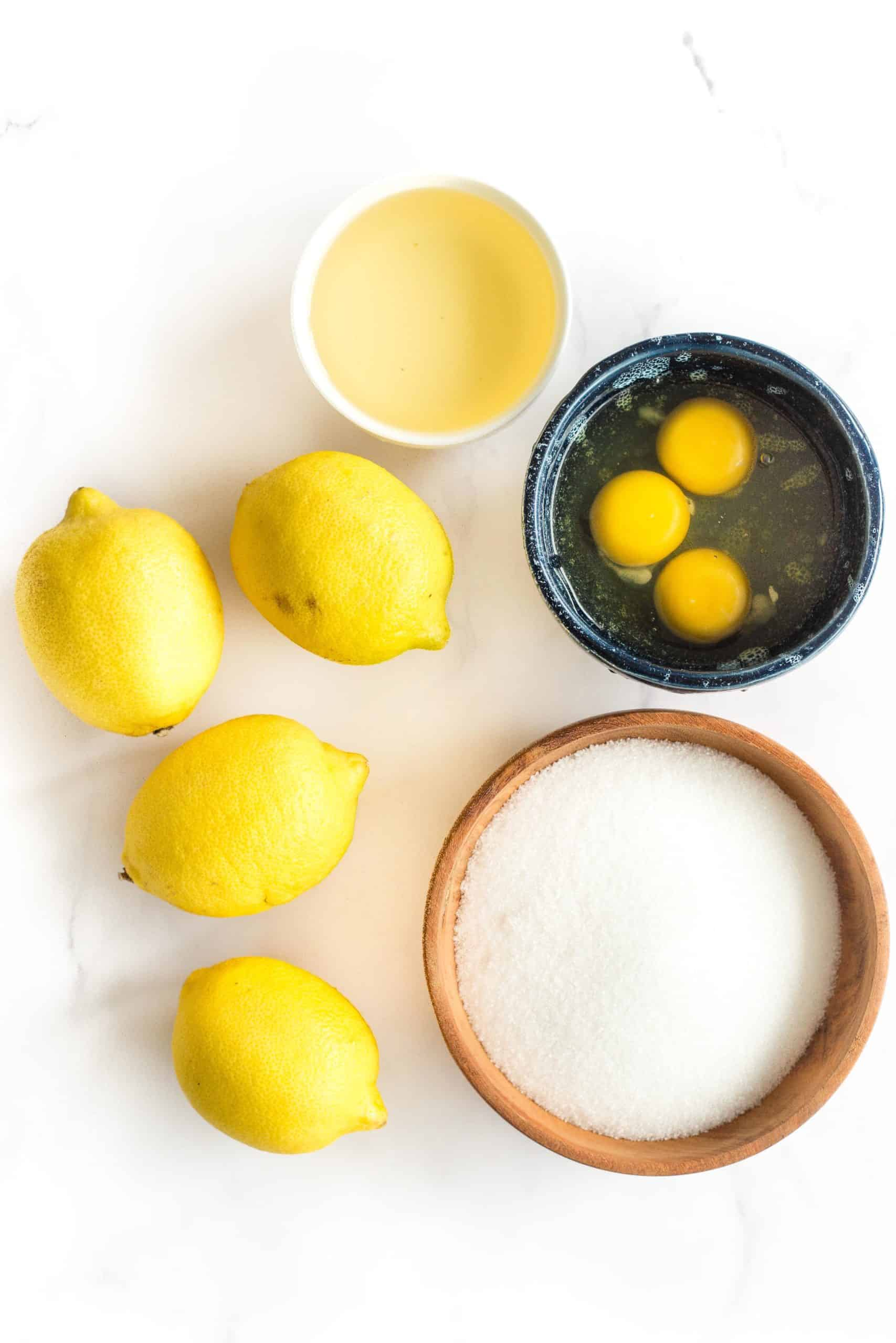 Ingredients for lemon curd laid out on a marble board.