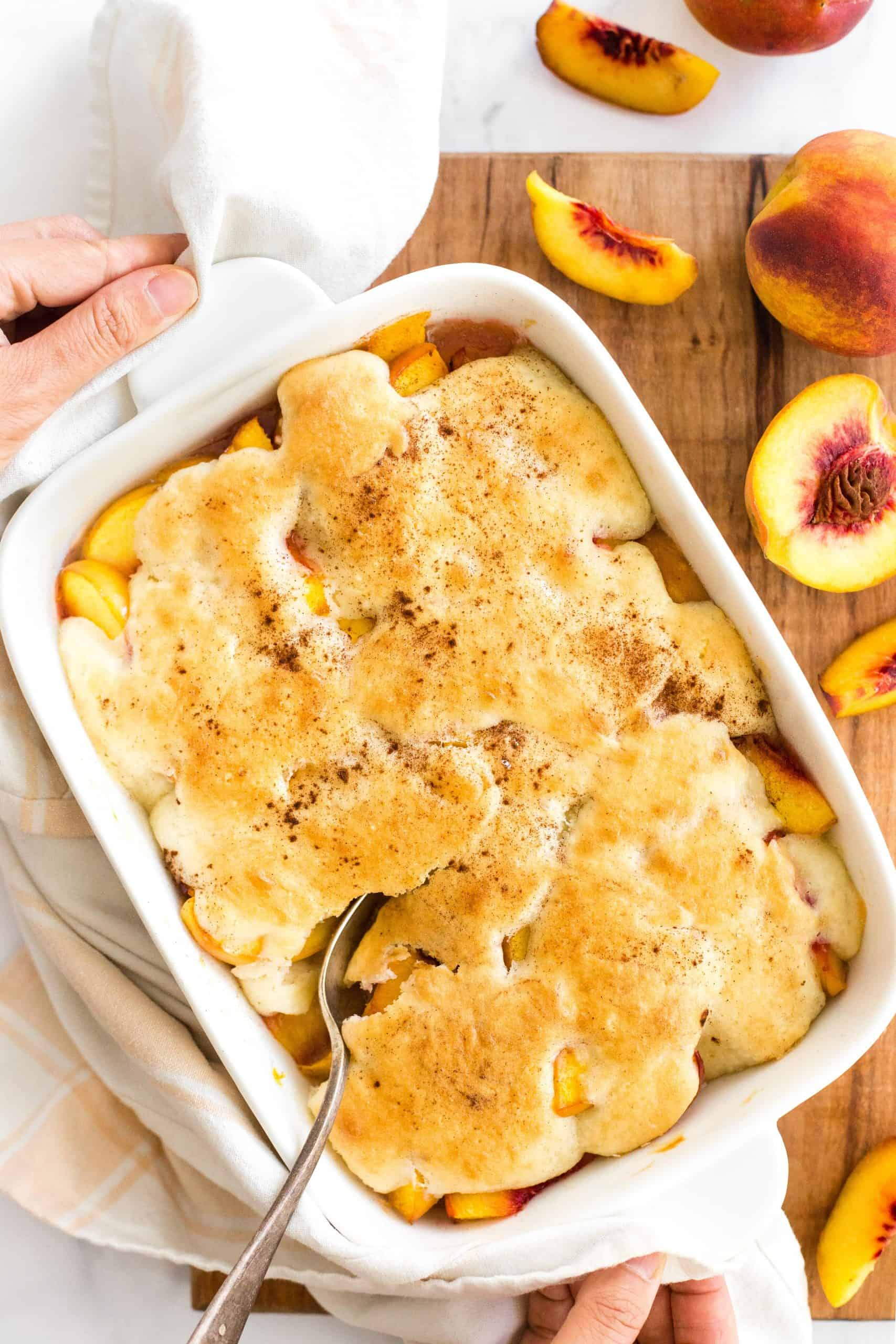 Two hands reaching for a cobbler-filled baking dish.