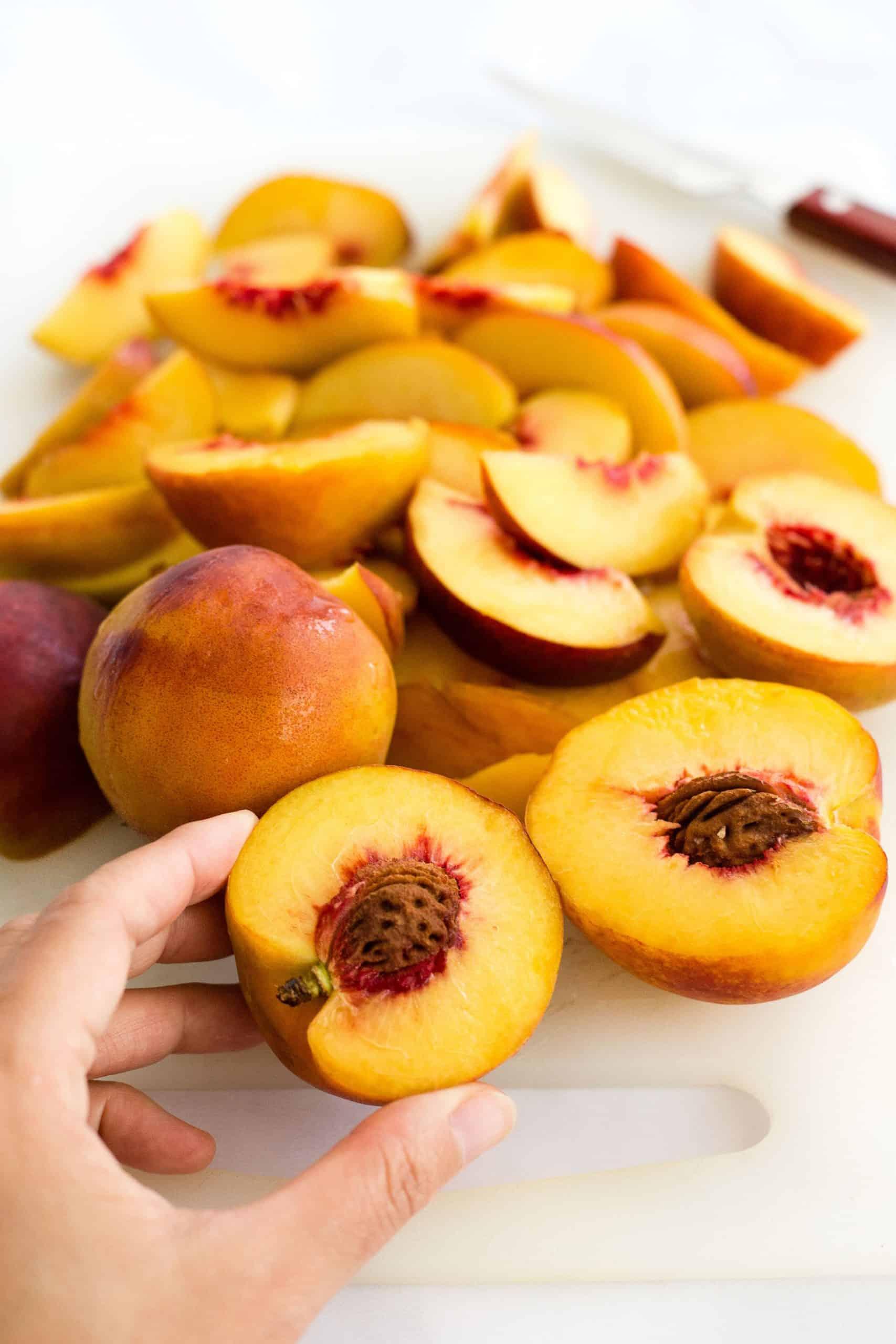 Hand holding a half-cut peach.