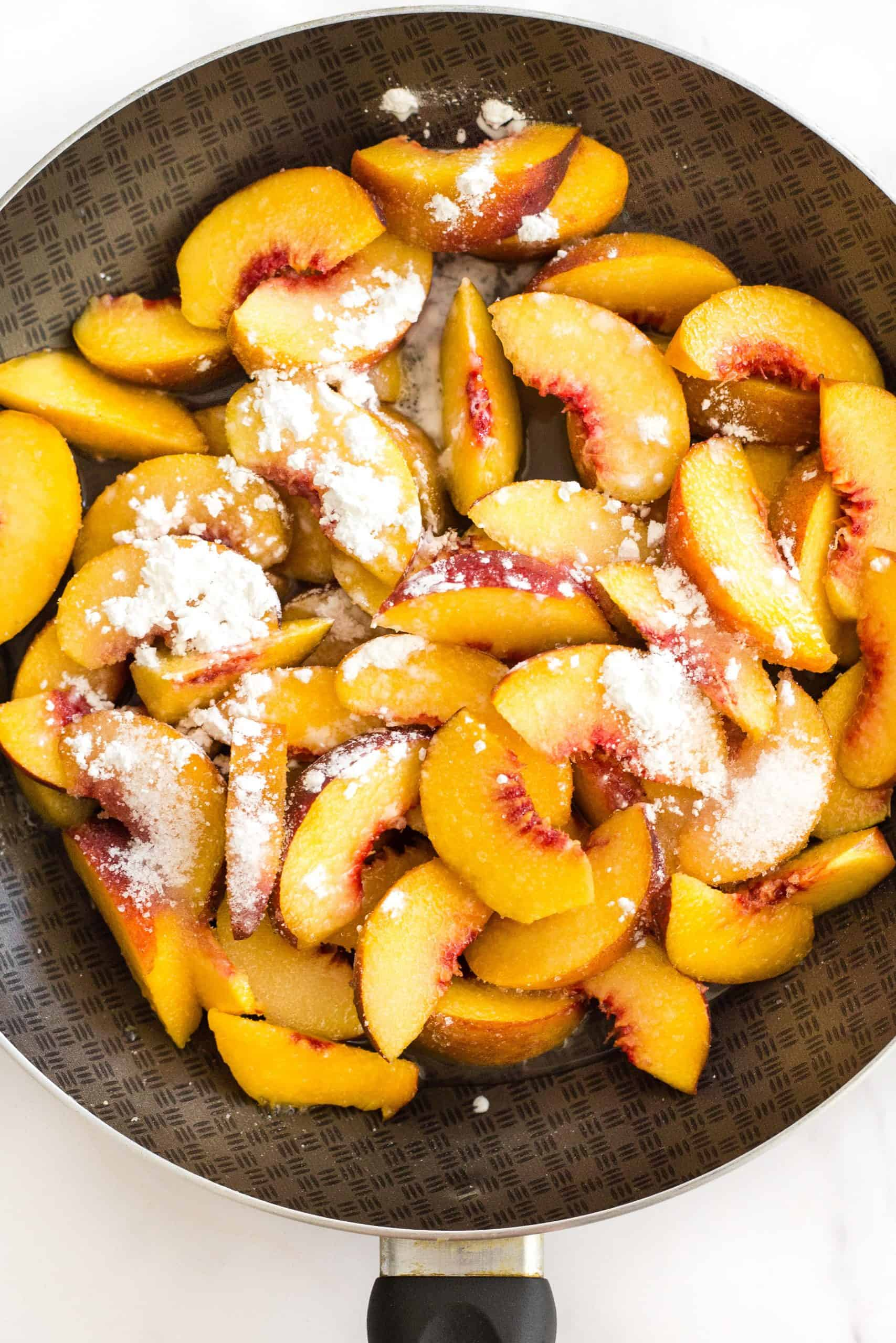 Sliced peaches and corn starch in a skillet.