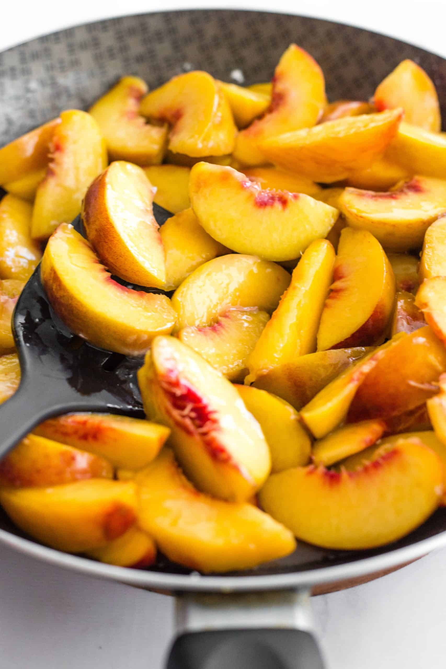 Cooked peach slices in a skillet with a spatula.