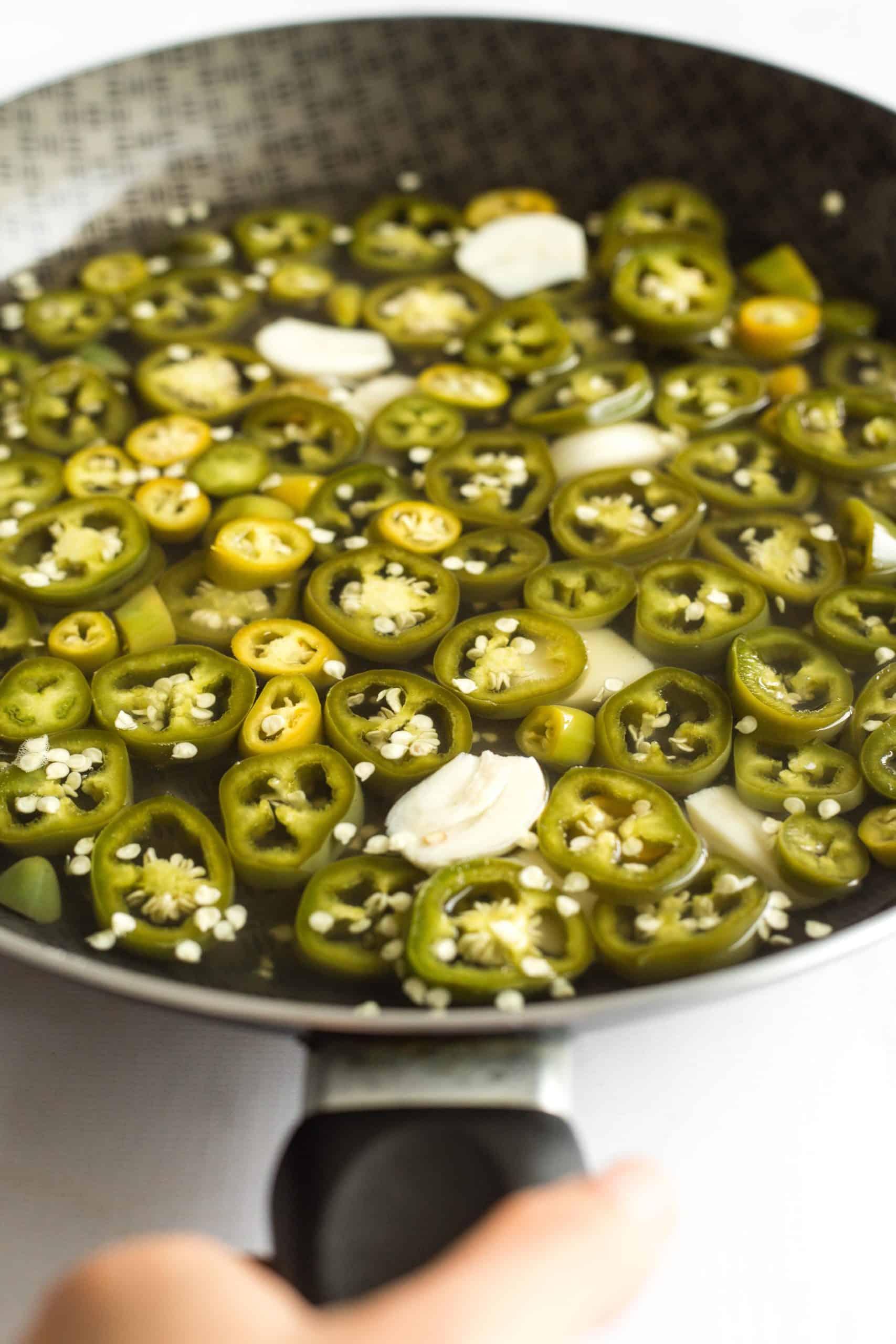 A large skillet of freshly pickled jalapeño peppers.