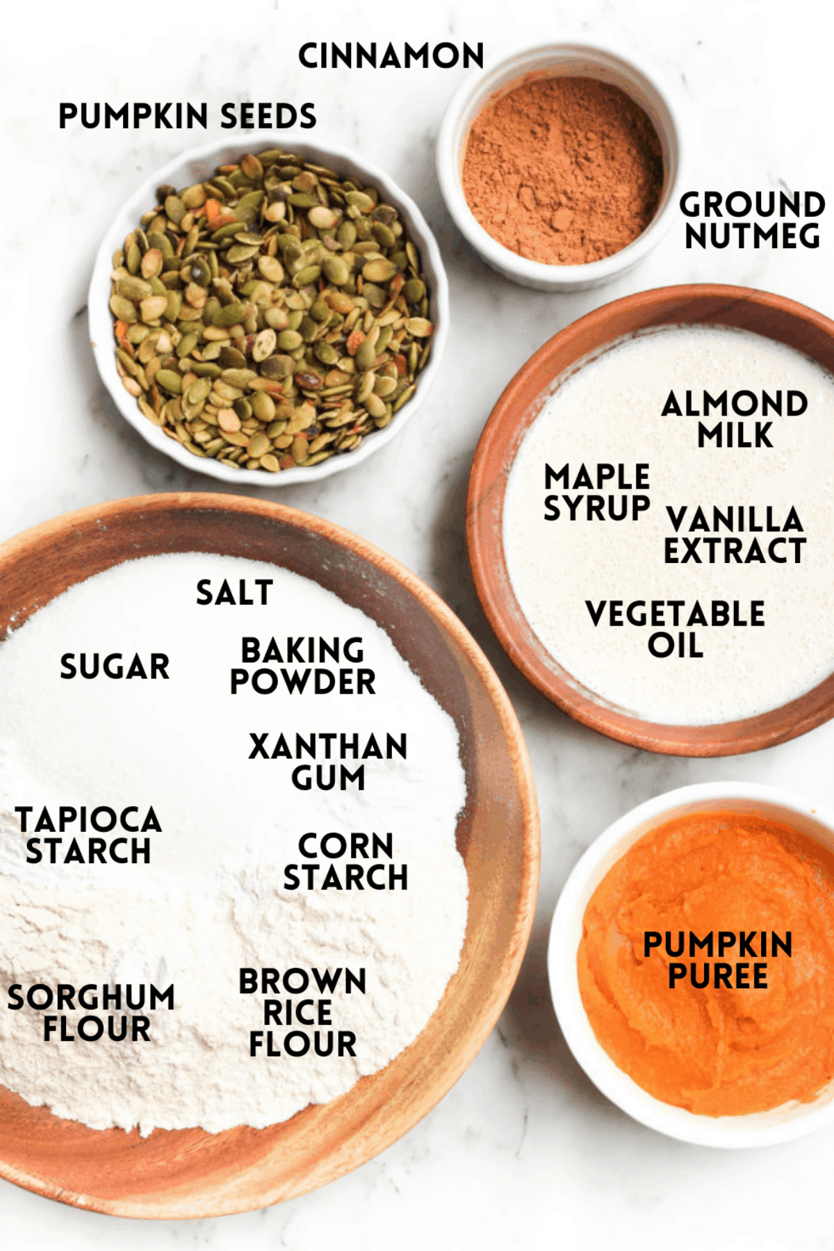Ingredients for pumpkin bread laid out on a marble board and labeled with text.