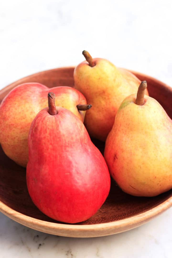 Red Anjou pears sitting in a wooden bowl.