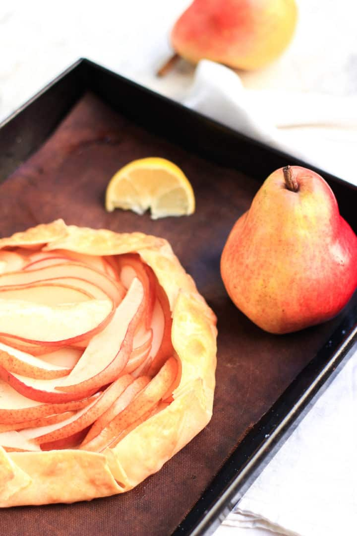 Freshly baked pear galette on a baking sheet alongside a red pear.