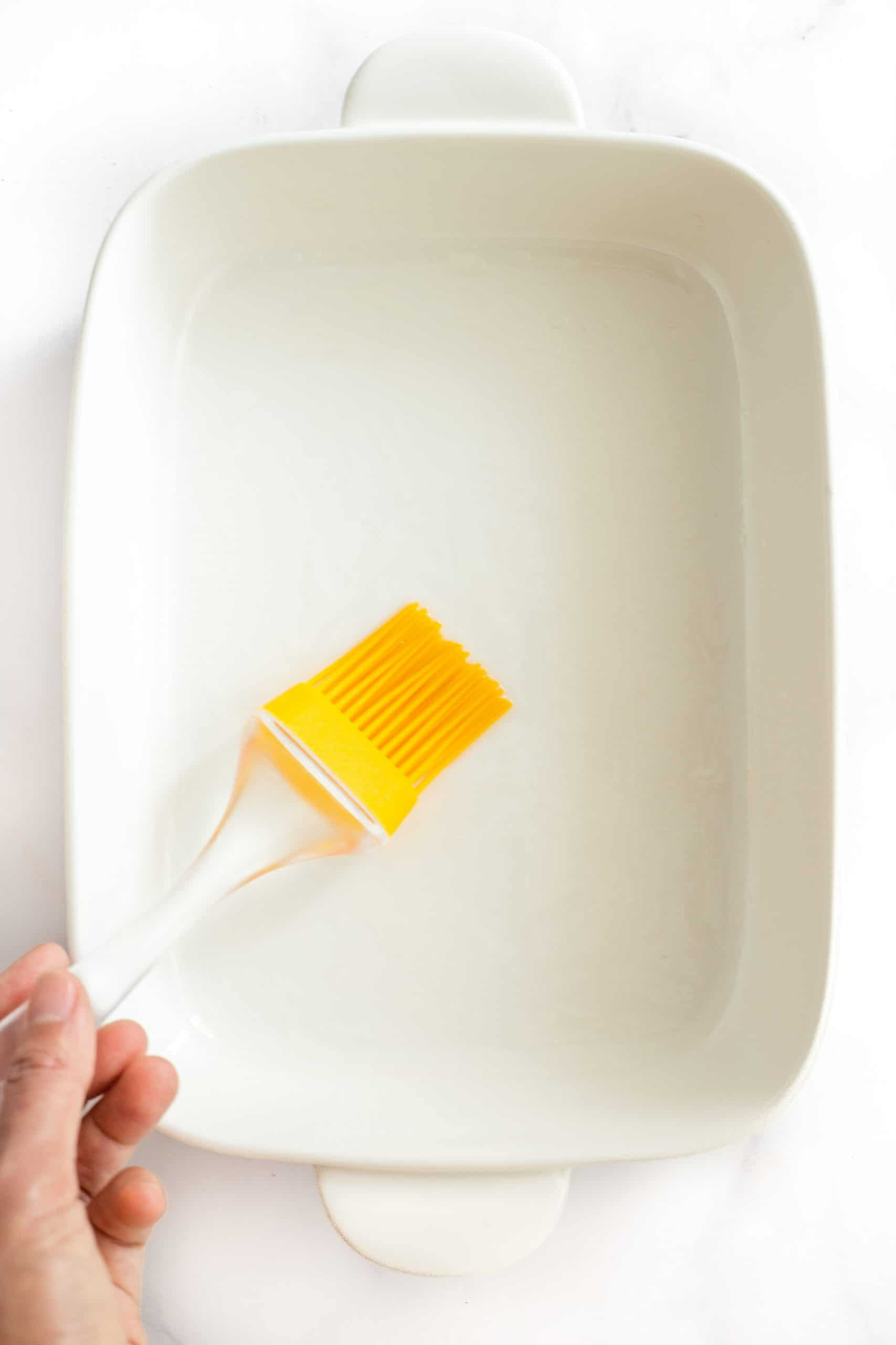 Greasing a casserole dish with oil.